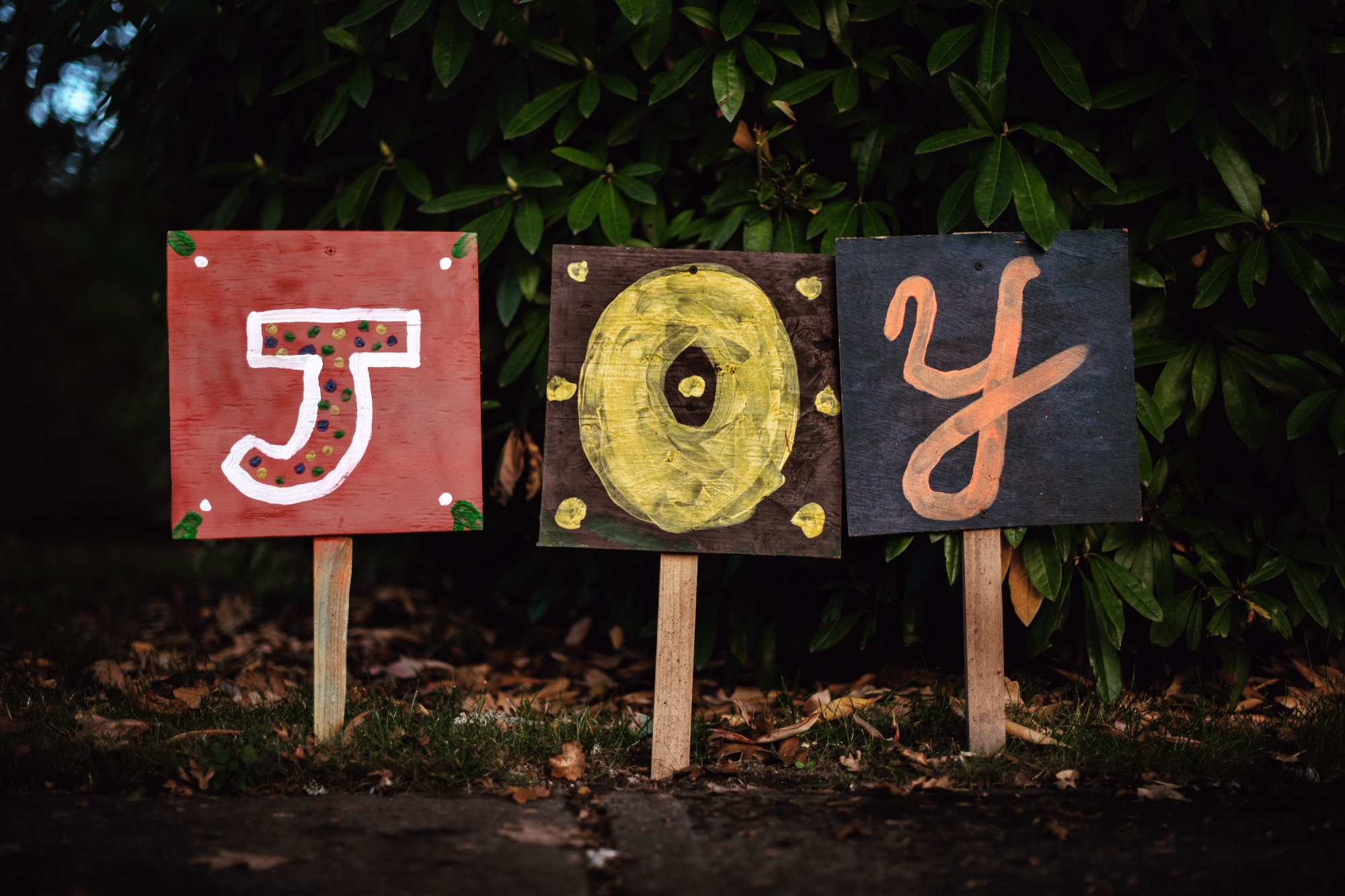 "Three signs next to each other, spelling out the word ""Joy"""