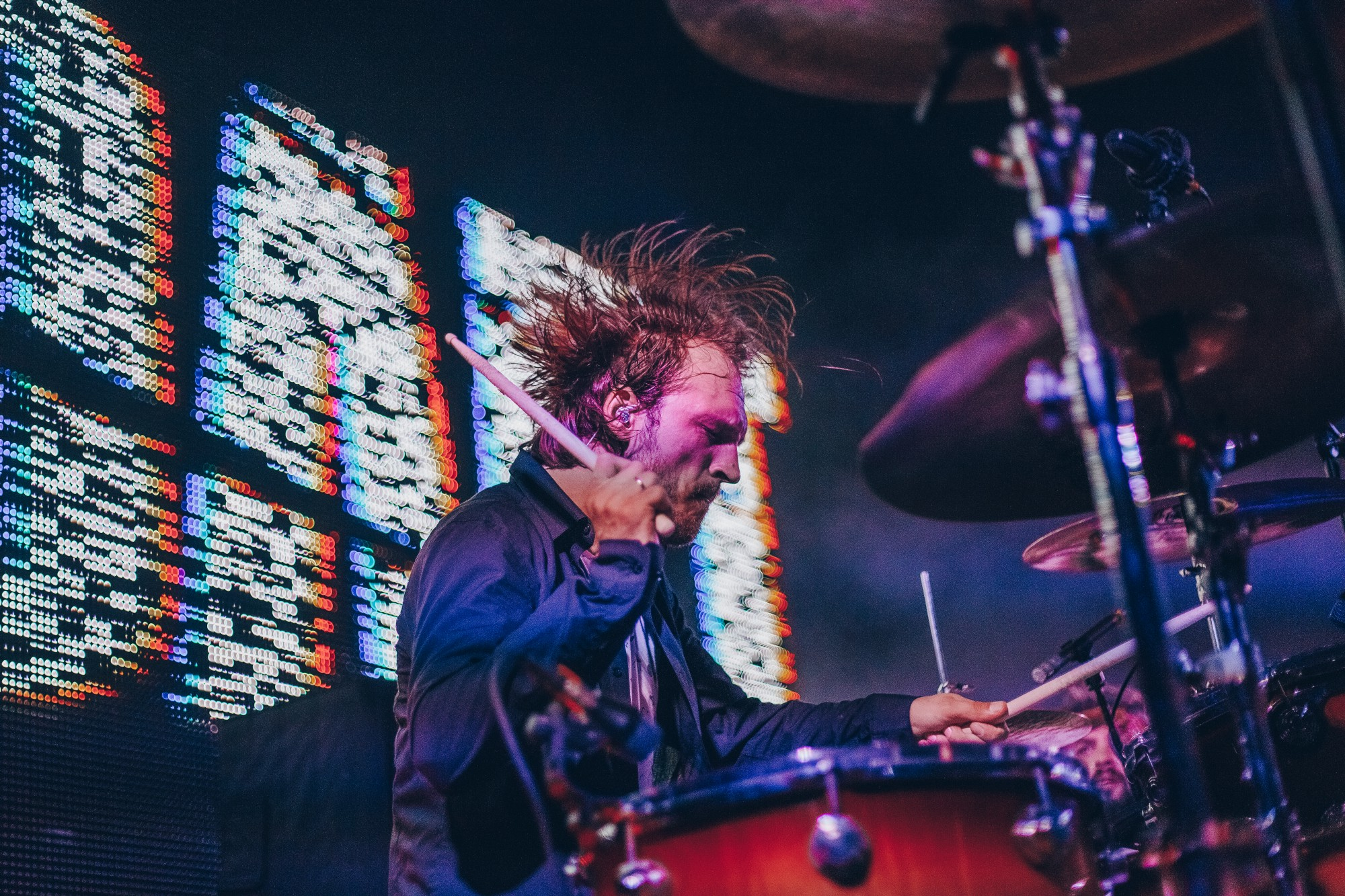 Male drummer on stage playing wildly with lights behind him. His hair is flying everywhere and he looks very concentrated.
