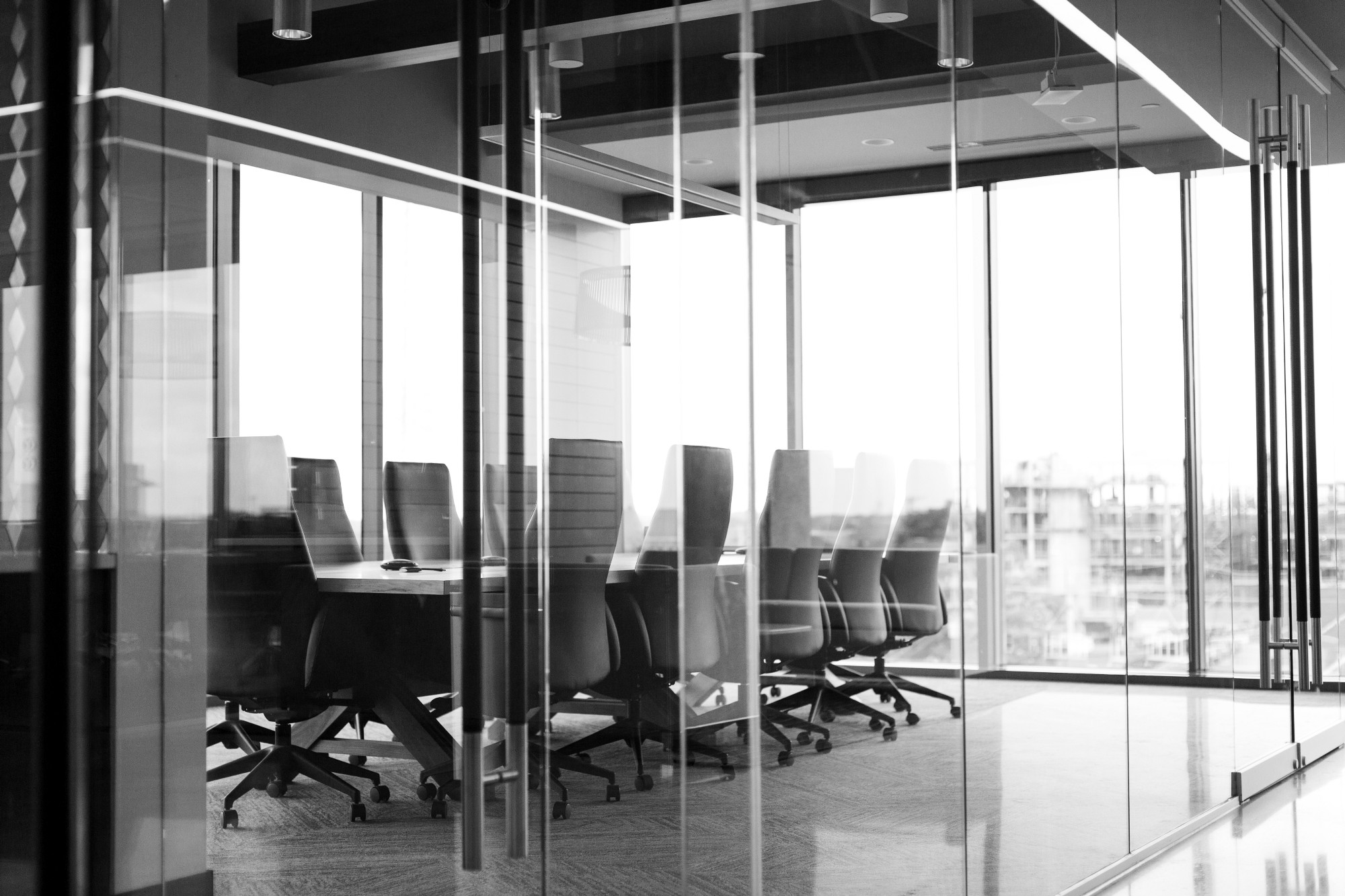 A stereotypical corporate board room, black-and-white.