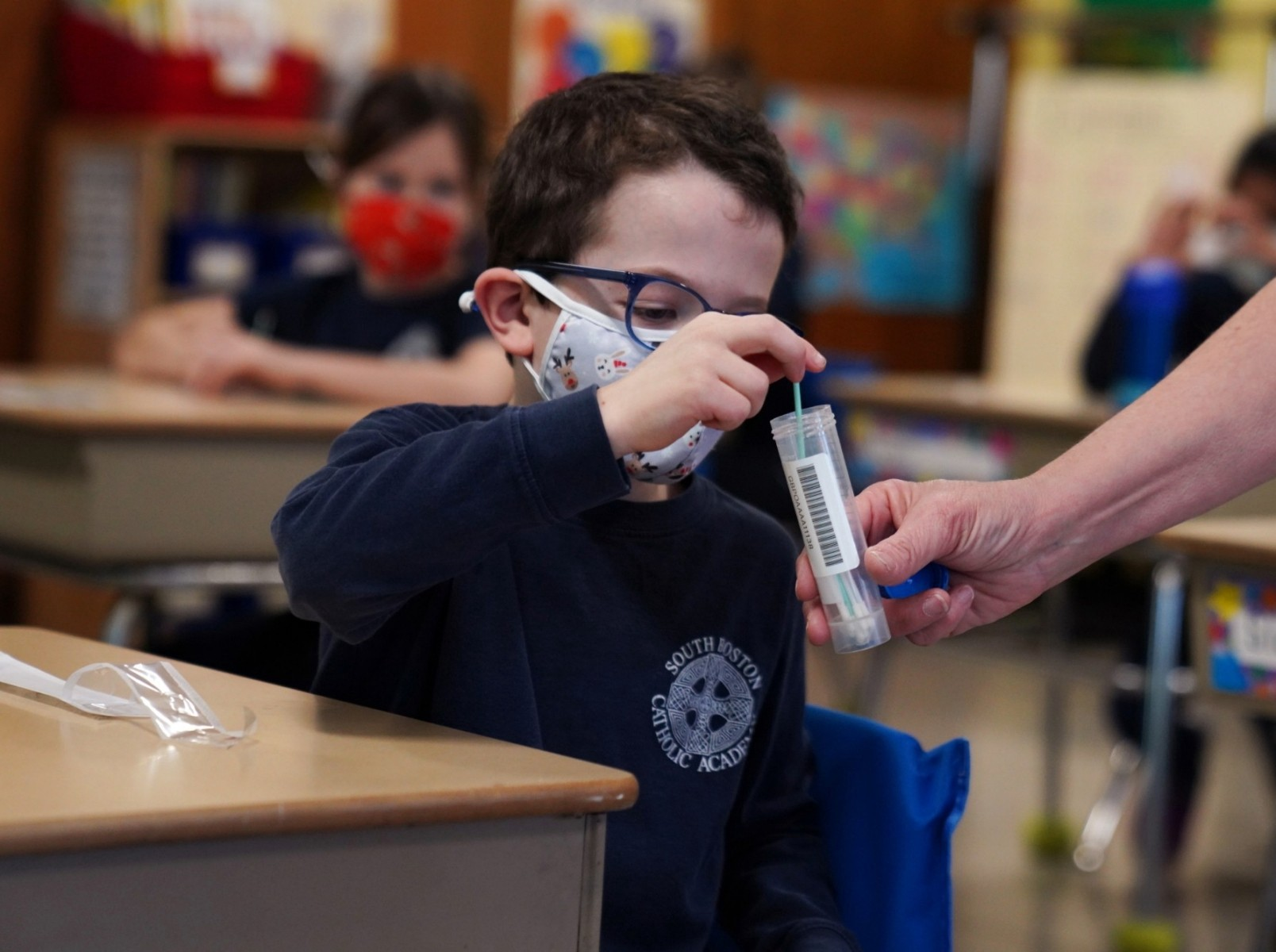 A child places his test swab in a vial at South Boston Catholic Academy in Boston, Massachusetts, January 28, 2021. Photo by Allison Dinner/Reuters