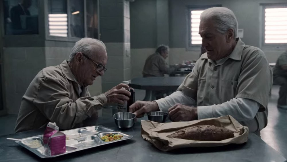 Two old male characters in The Irishman eat food in prison
