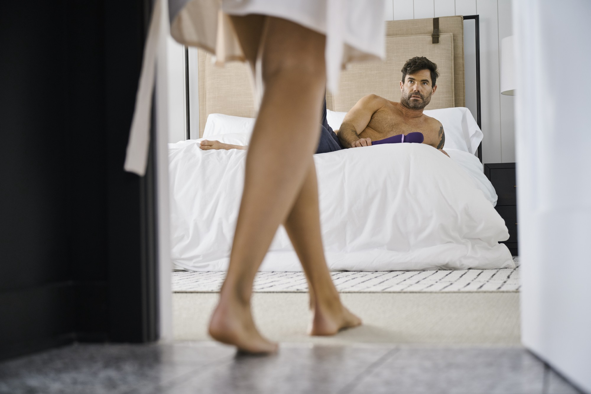 A shot through a hotel room door. We see a woman's legs as she enters wearing a white robe. Through the door we see a man waiting, topless on the bed.