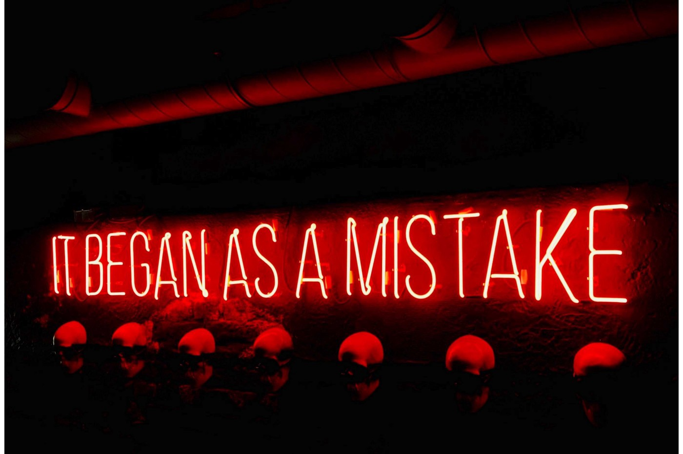 """Red neon sign saying, """"IT BEGAN AS A MISTAKE."""""""