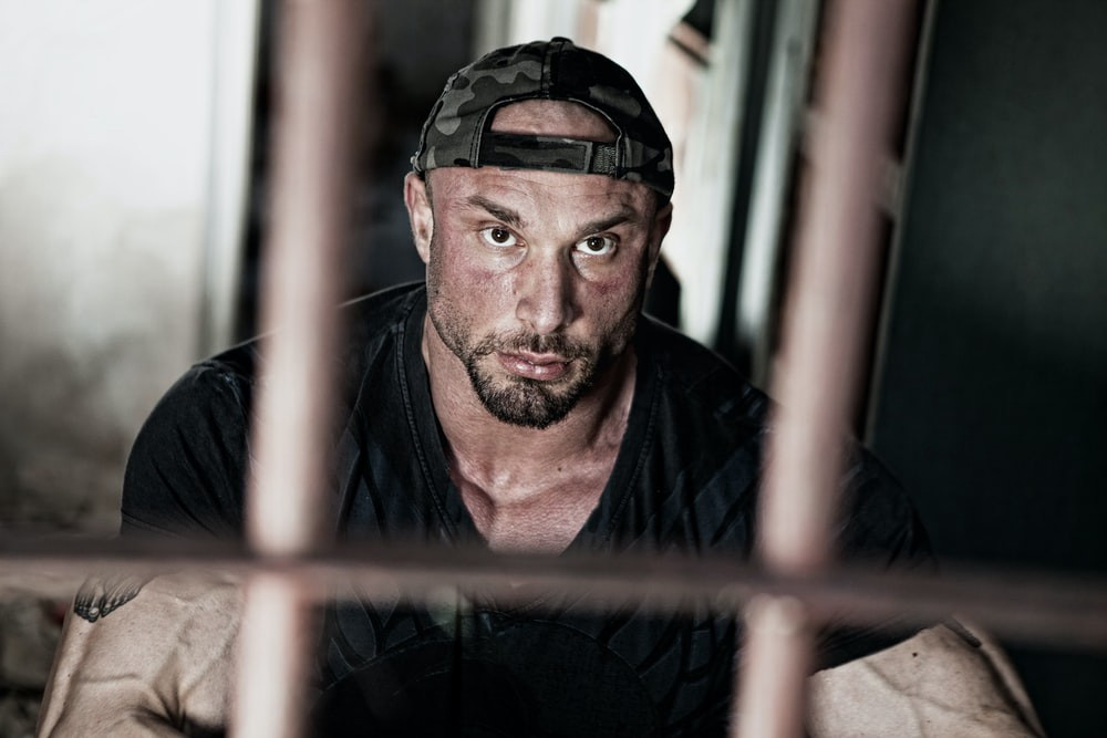 A big muscular guy with a dark goatee in a black t-shirt and ball cap on backwards-looking out from behind prison bars
