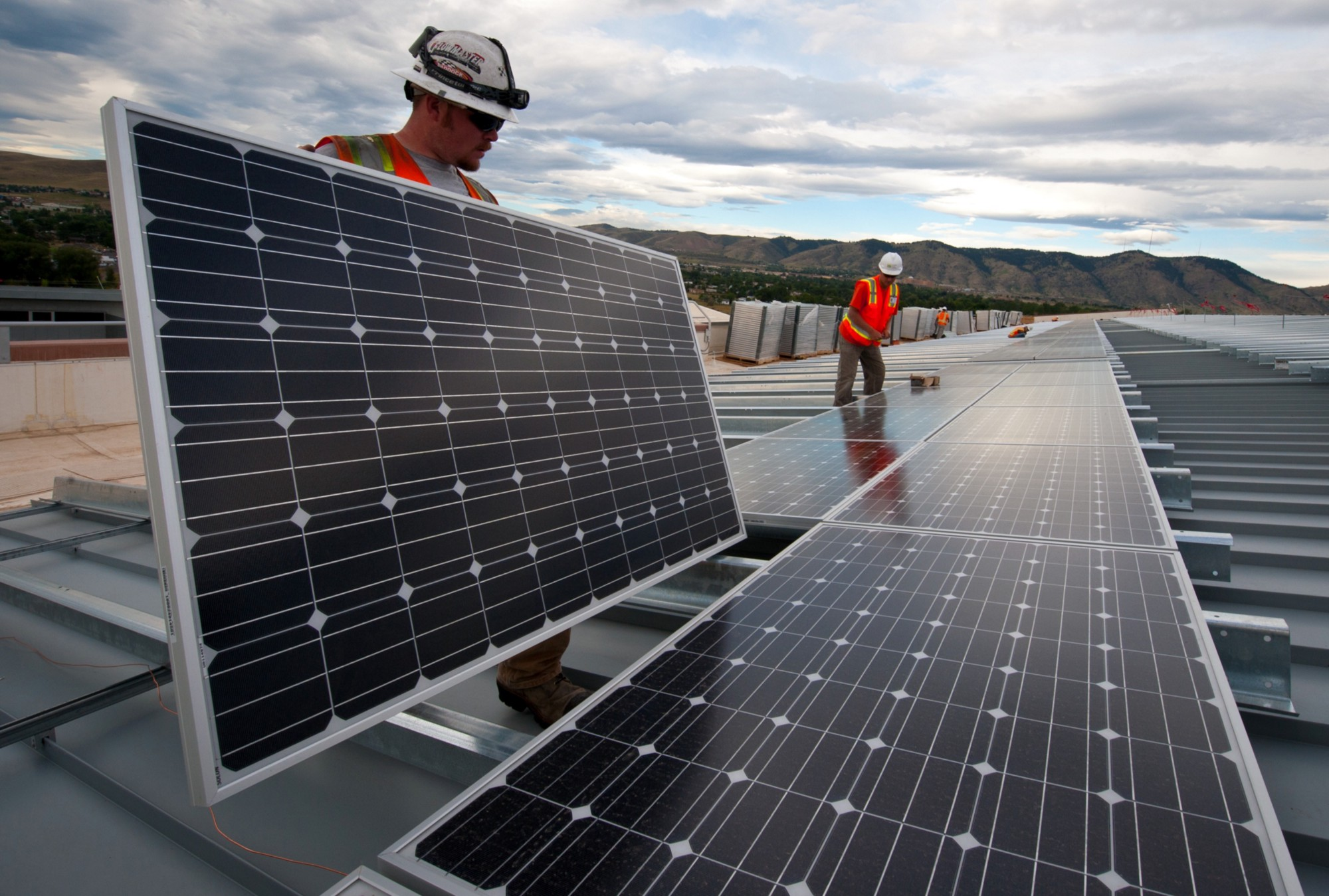 Workers installing solar panels on a rooftop