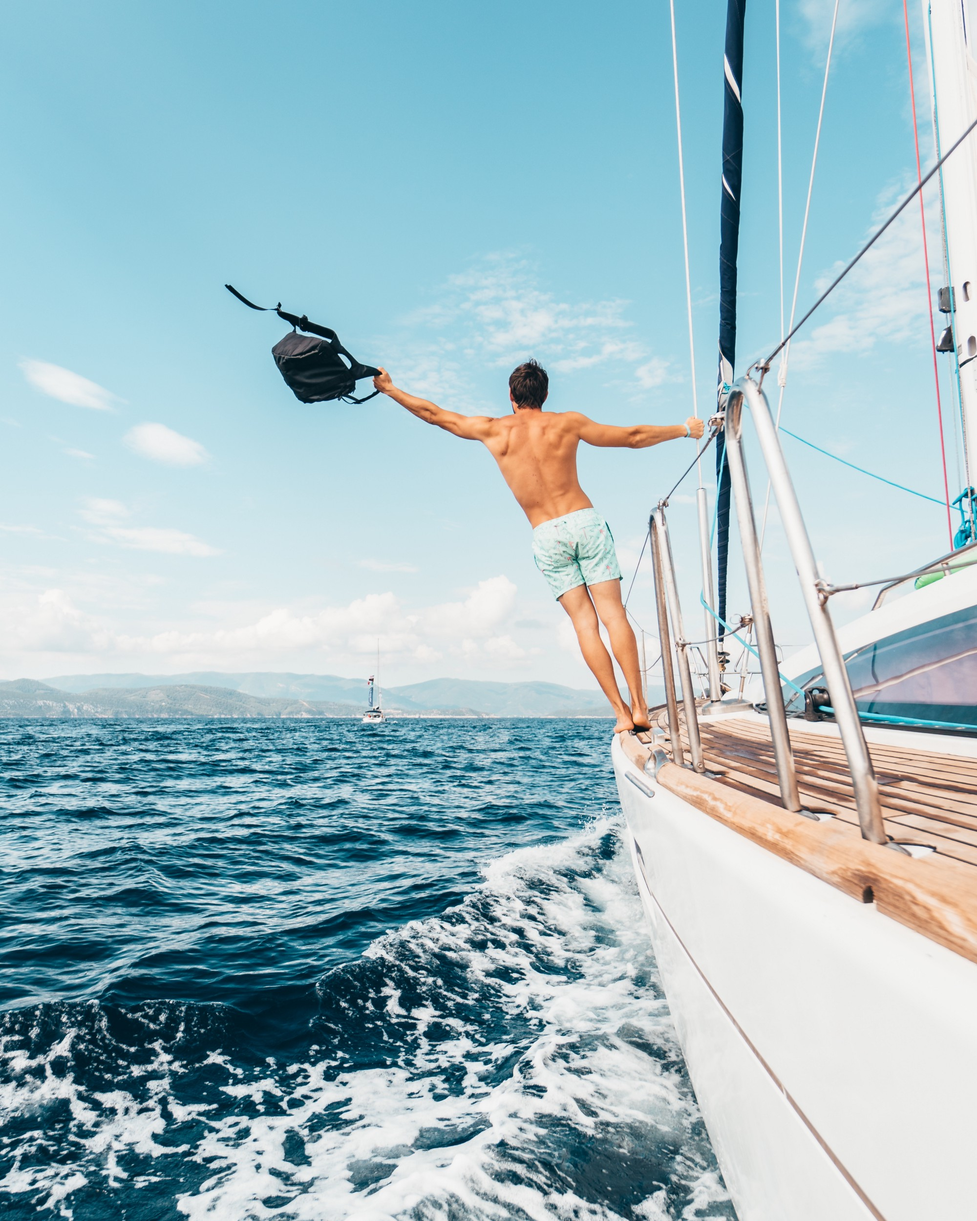 A topless man stands on the edge of the yacht while waving his backpack