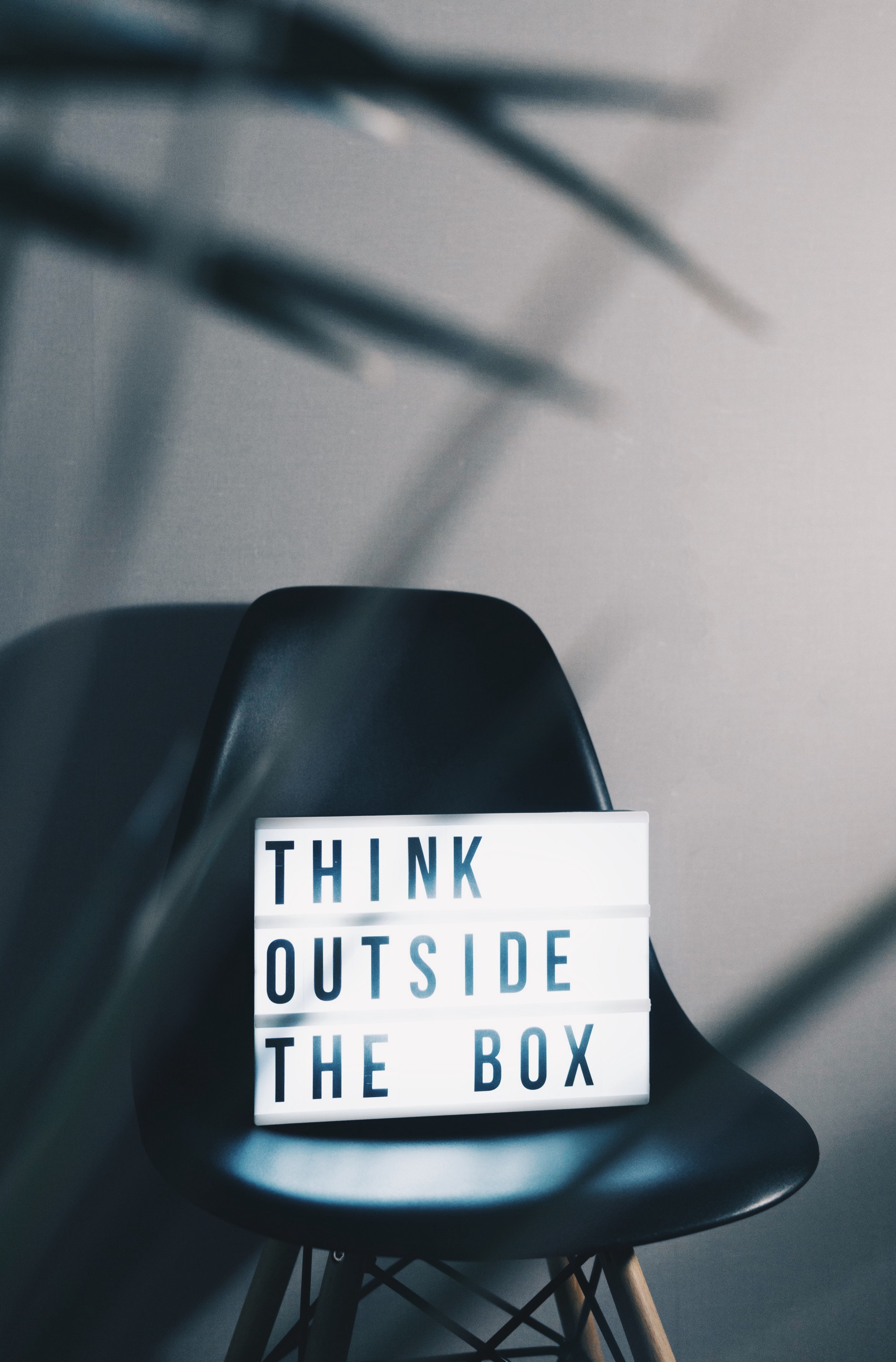 """Think outside the box"" is written on a box and placed on top of a black chair"