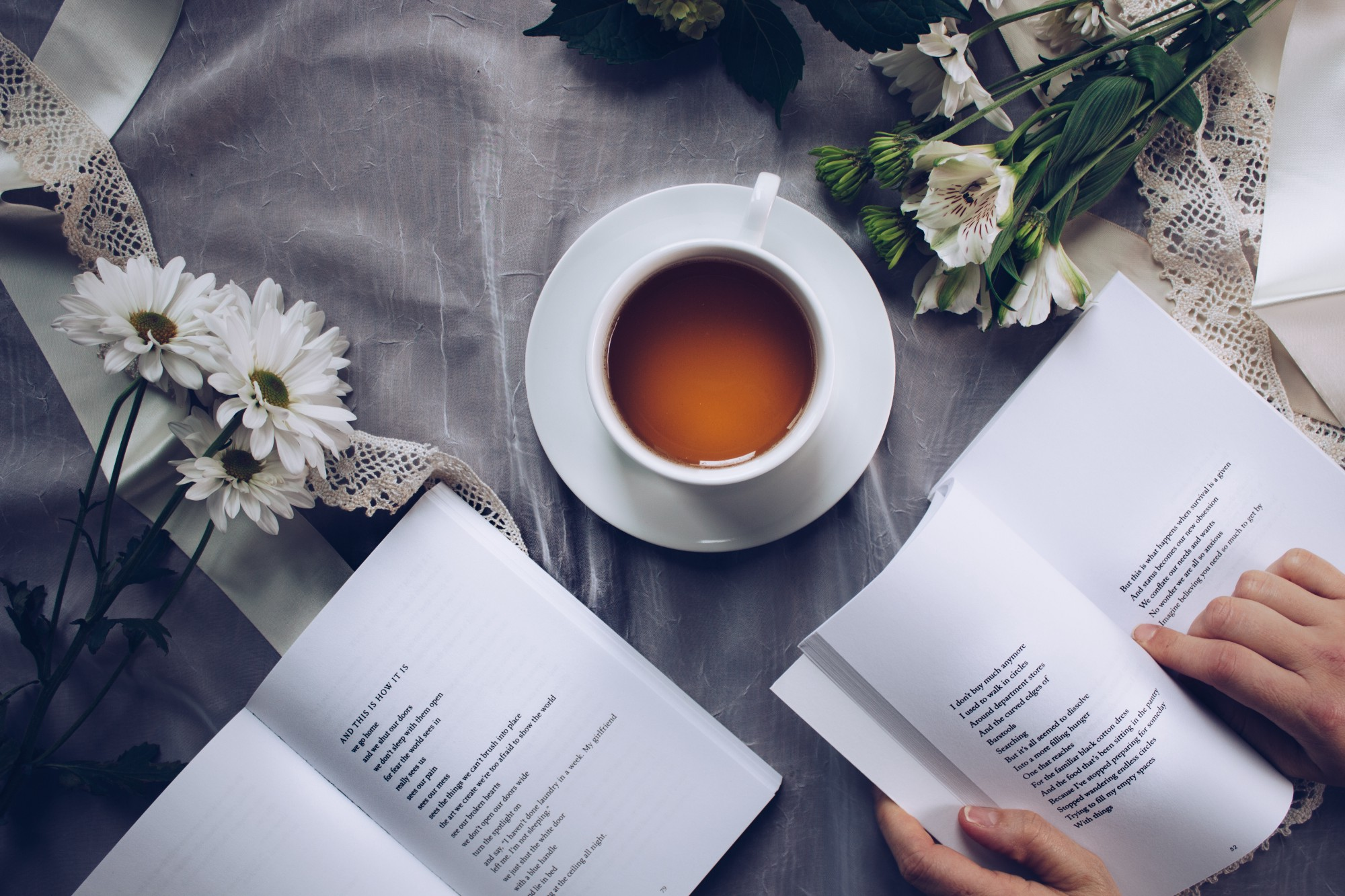 A cup of tea, books of poems, and flowers on a table with a gray tablecloth