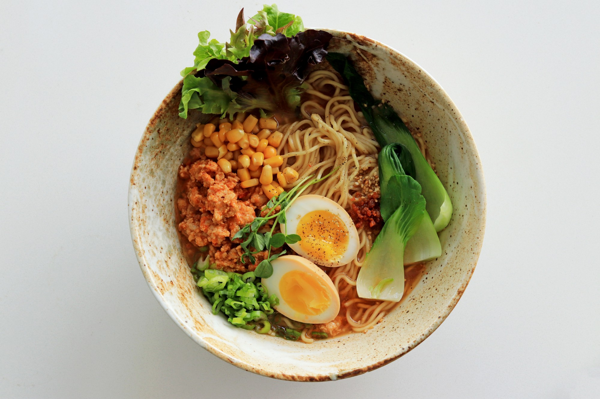 Ramen noodles with hardboiled egg, bok choy, lettuce, and other toppings.