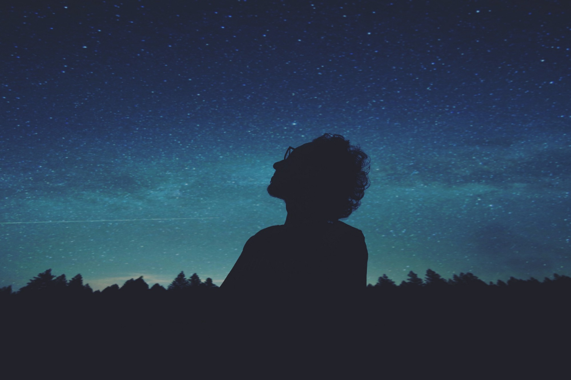 Silhouette of person with curly hair and glasses staring thoughtfully into a starlit night sky.