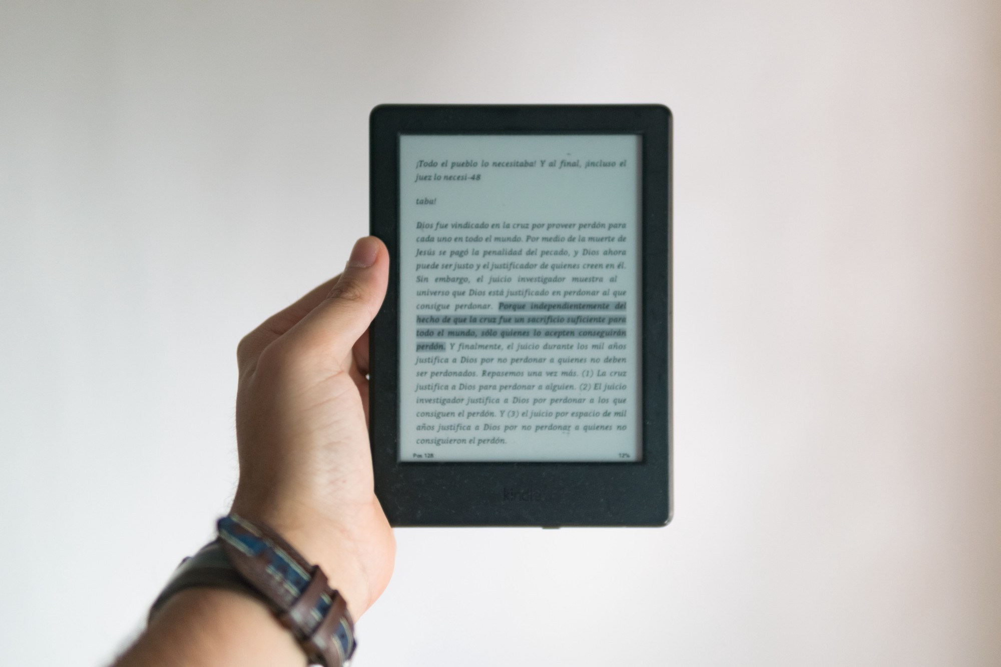 A stretched-out hand holding a Kindle eReader.