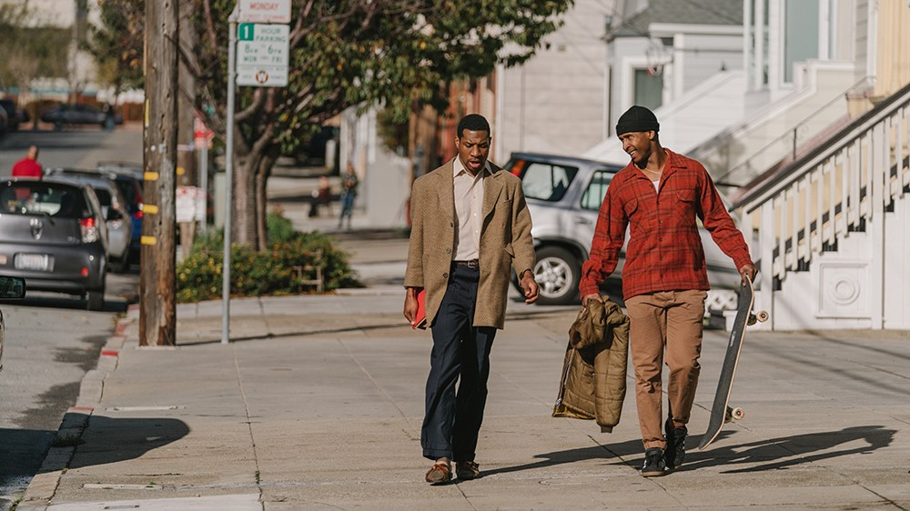 Jonathan Majors wearing a suit jacket and Jimmie Fails wearing a red flannel carrying a skateboard on a street