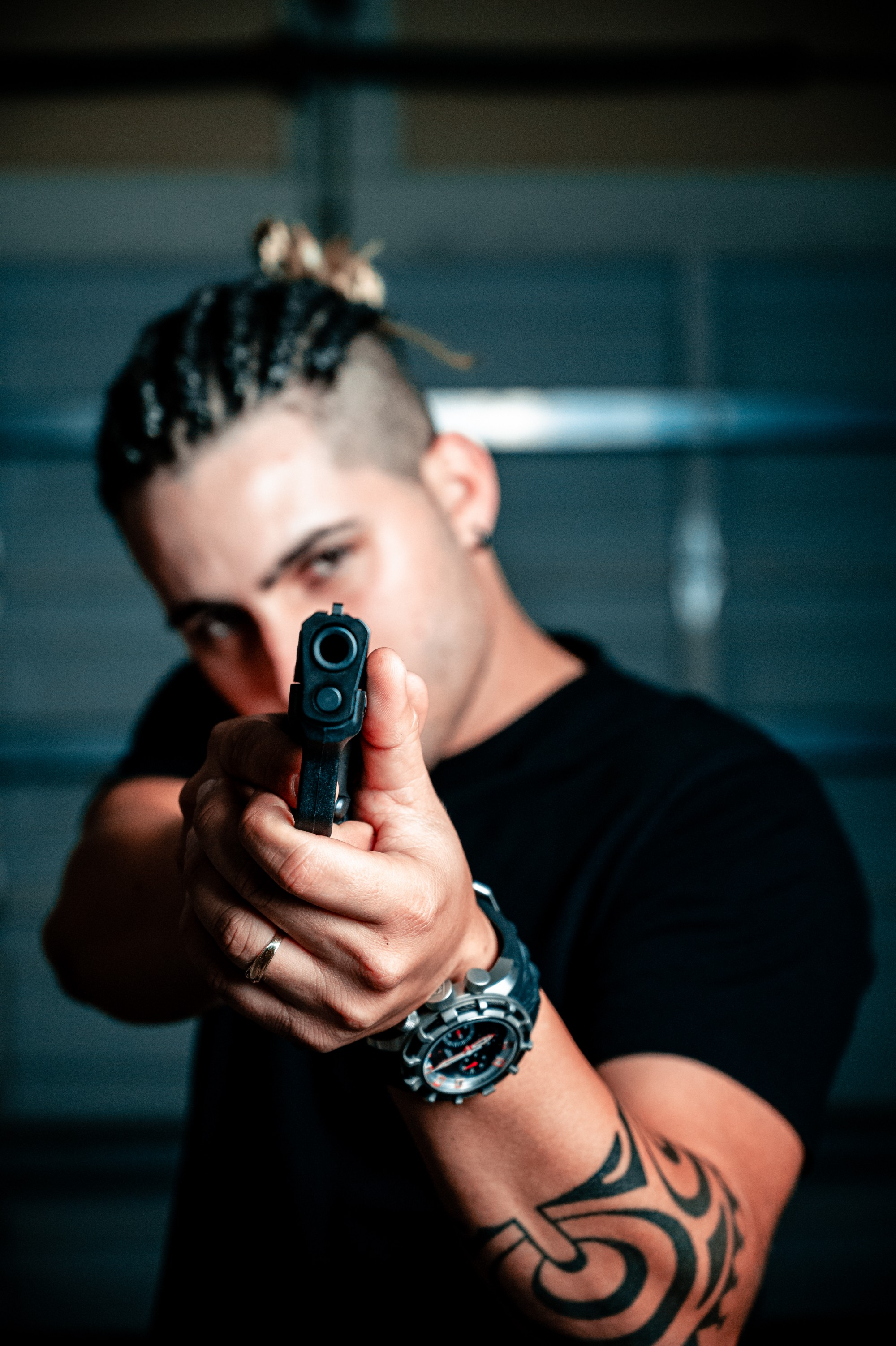 man pointing a gun at you, he has a tattoo on his left forearm