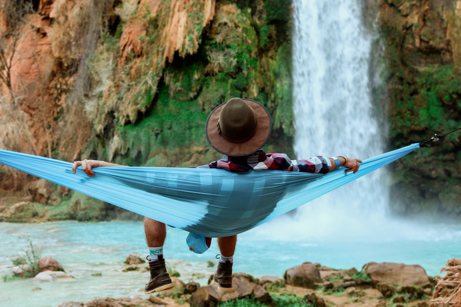A man sitting in a hammock facing away from the camera and towards a waterfall.
