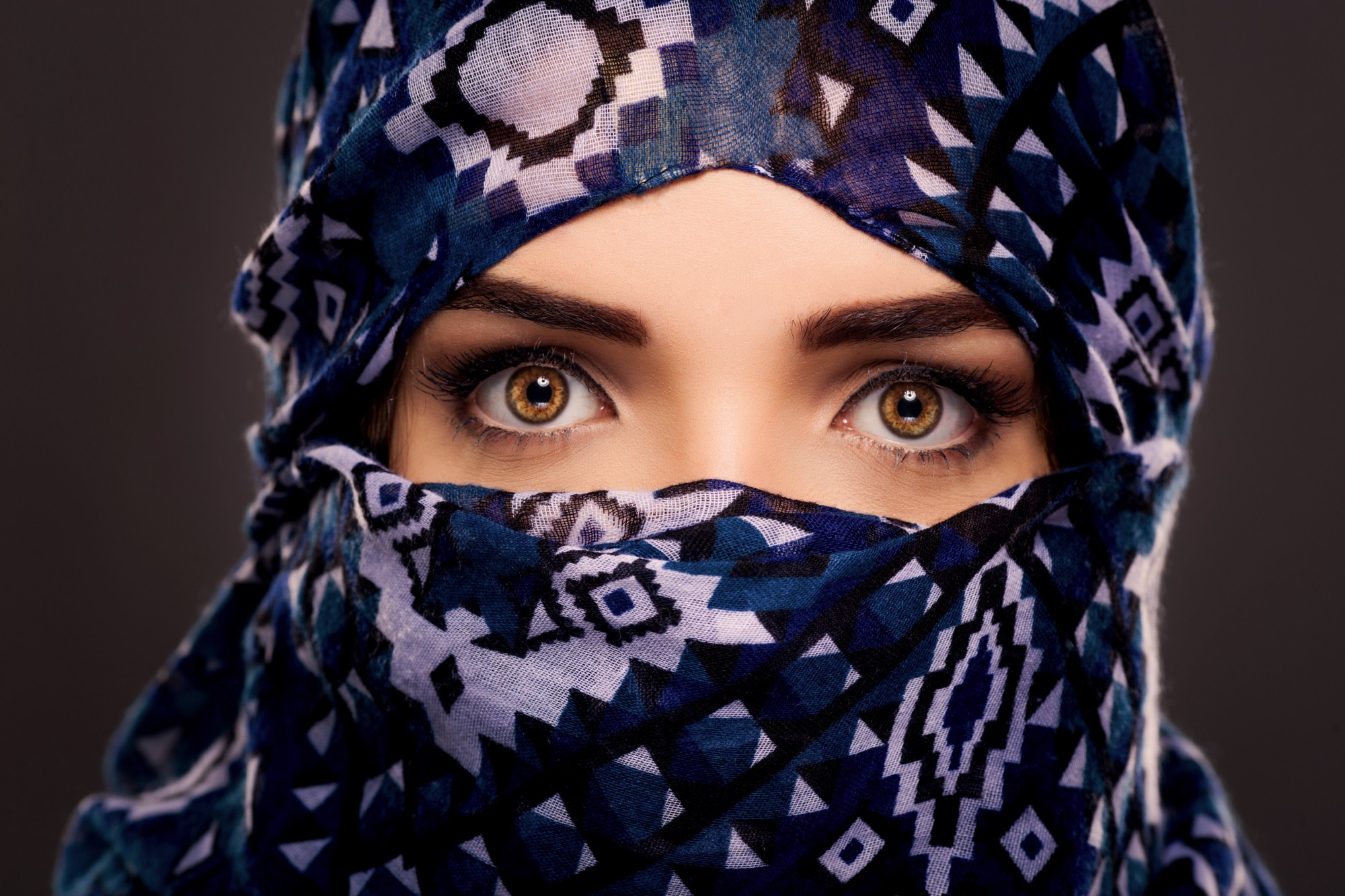A woman with a head covering that only leaves her brown eyes exposed.