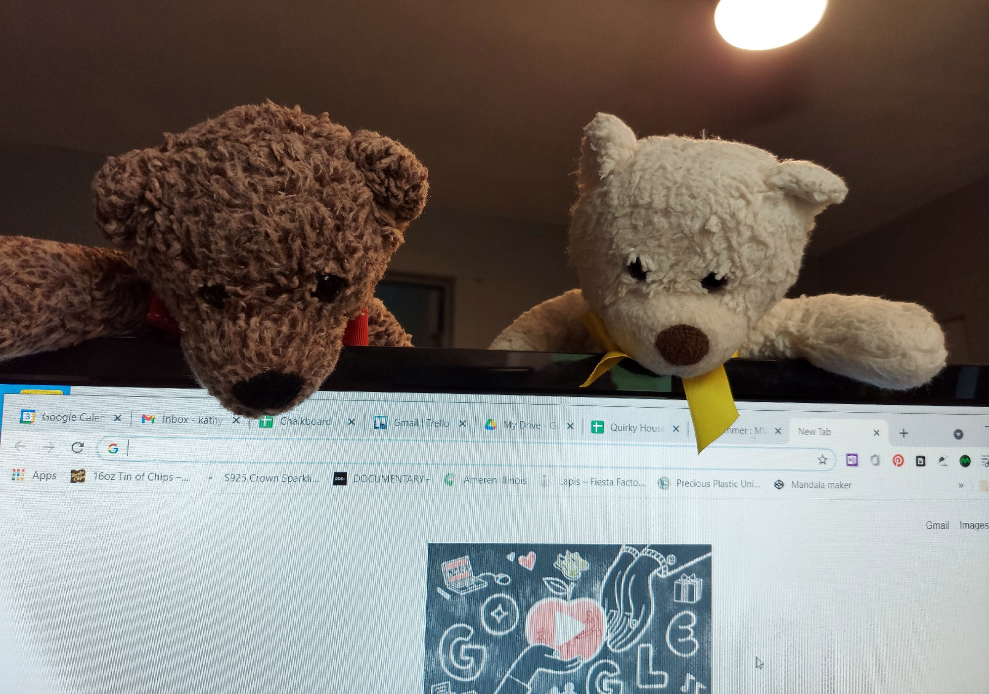 Two of my small teddy bears looking down on a computer monitor