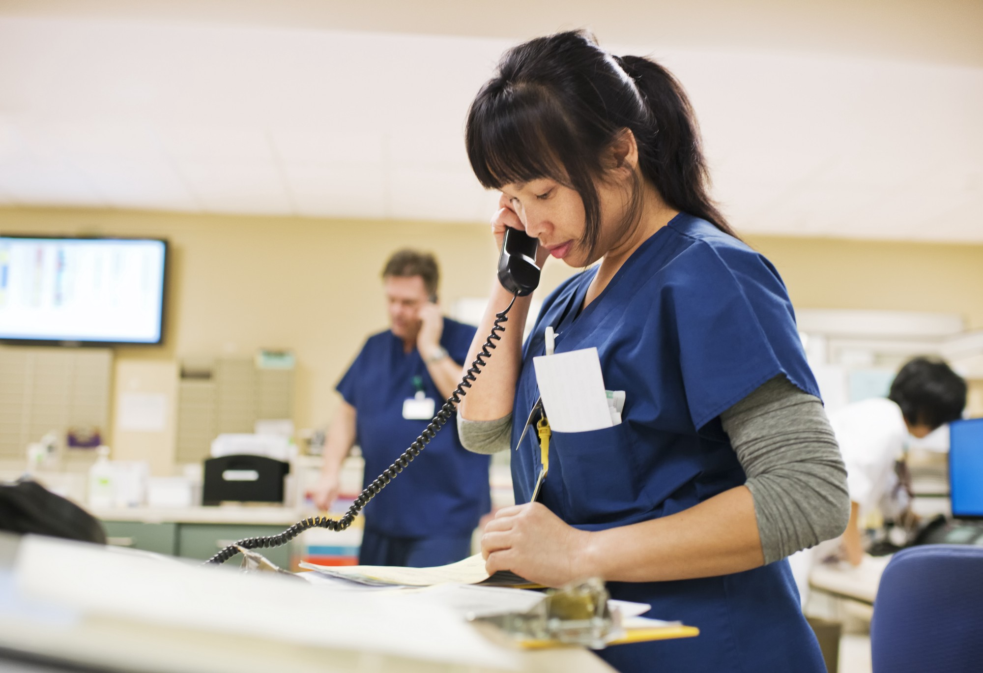 A photo of a clinical setting with three people in scrubs doing administration. In the foreground a nurse is on the phone.