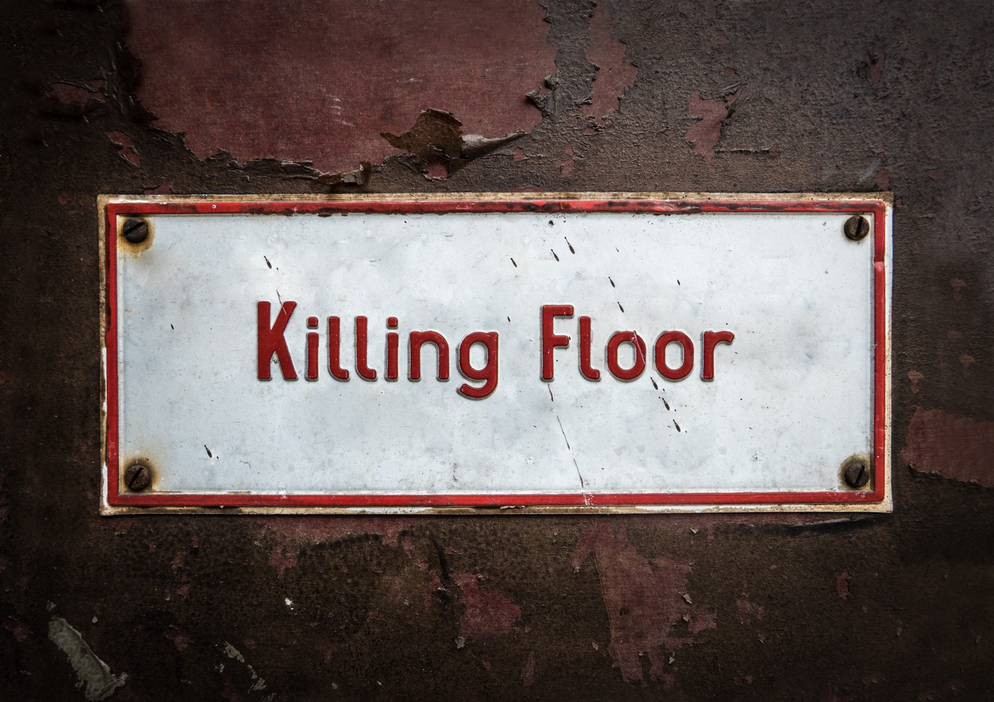 """A white metal sign that reads """"Killing Floor"""" in red lettering."""