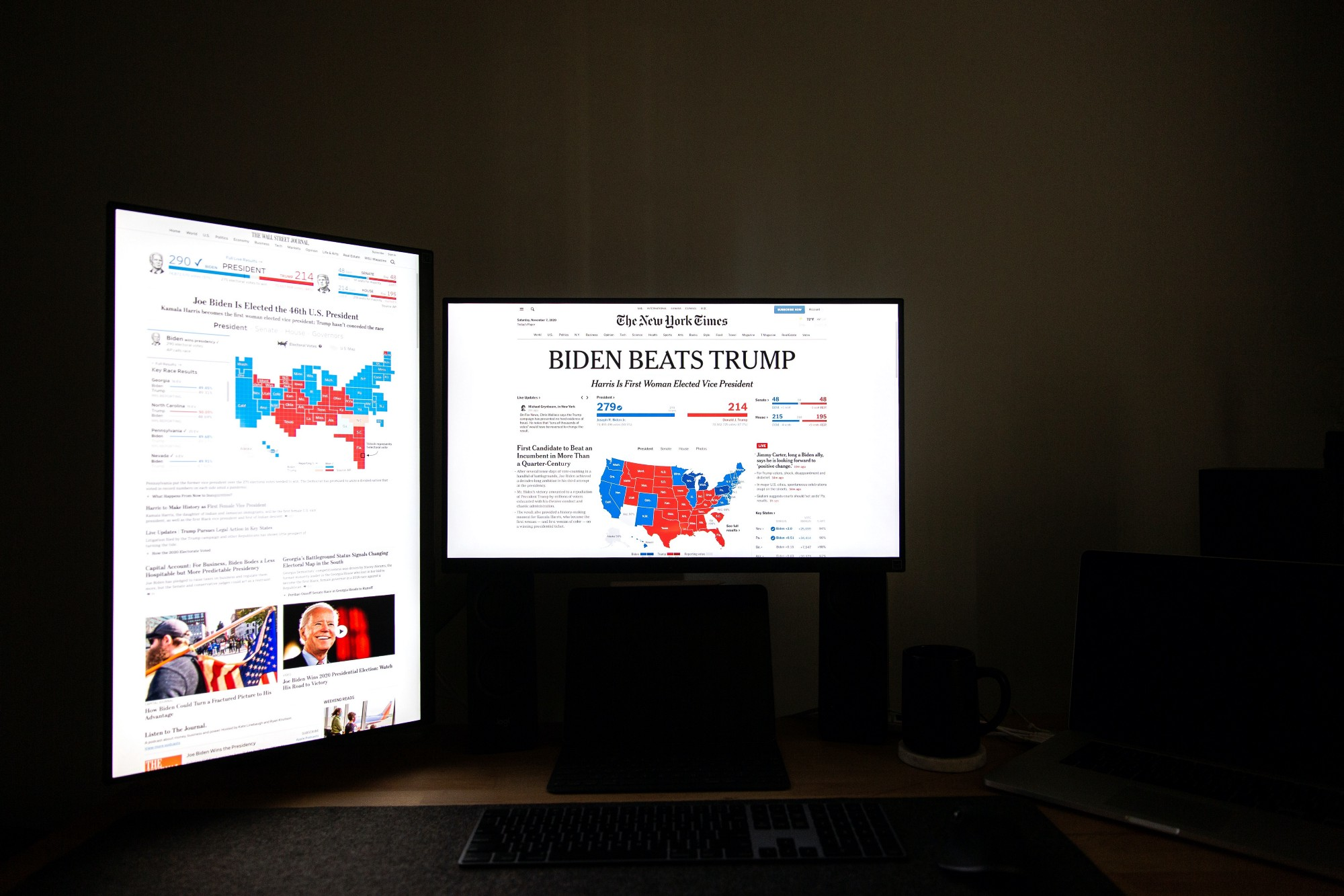 Two computer screens with headlines announcing Biden's win