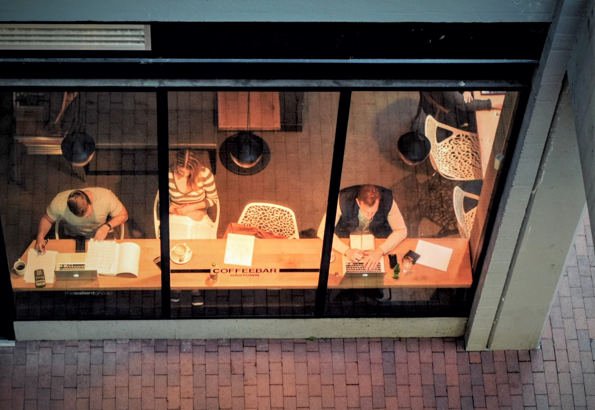 birdseye view through large windows of people working at common desk