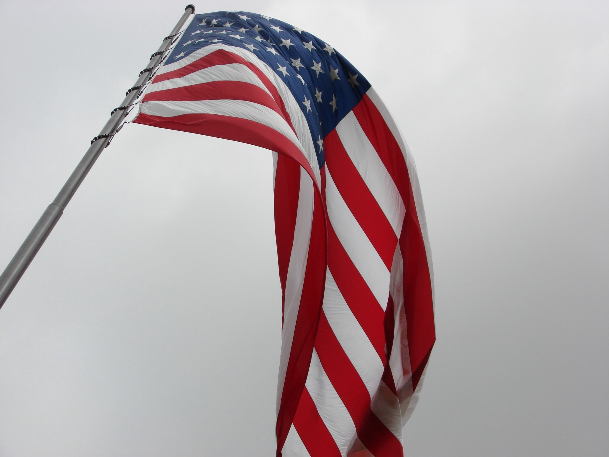 looking up at a USA flag on a flag pole, flying on a cloudy day