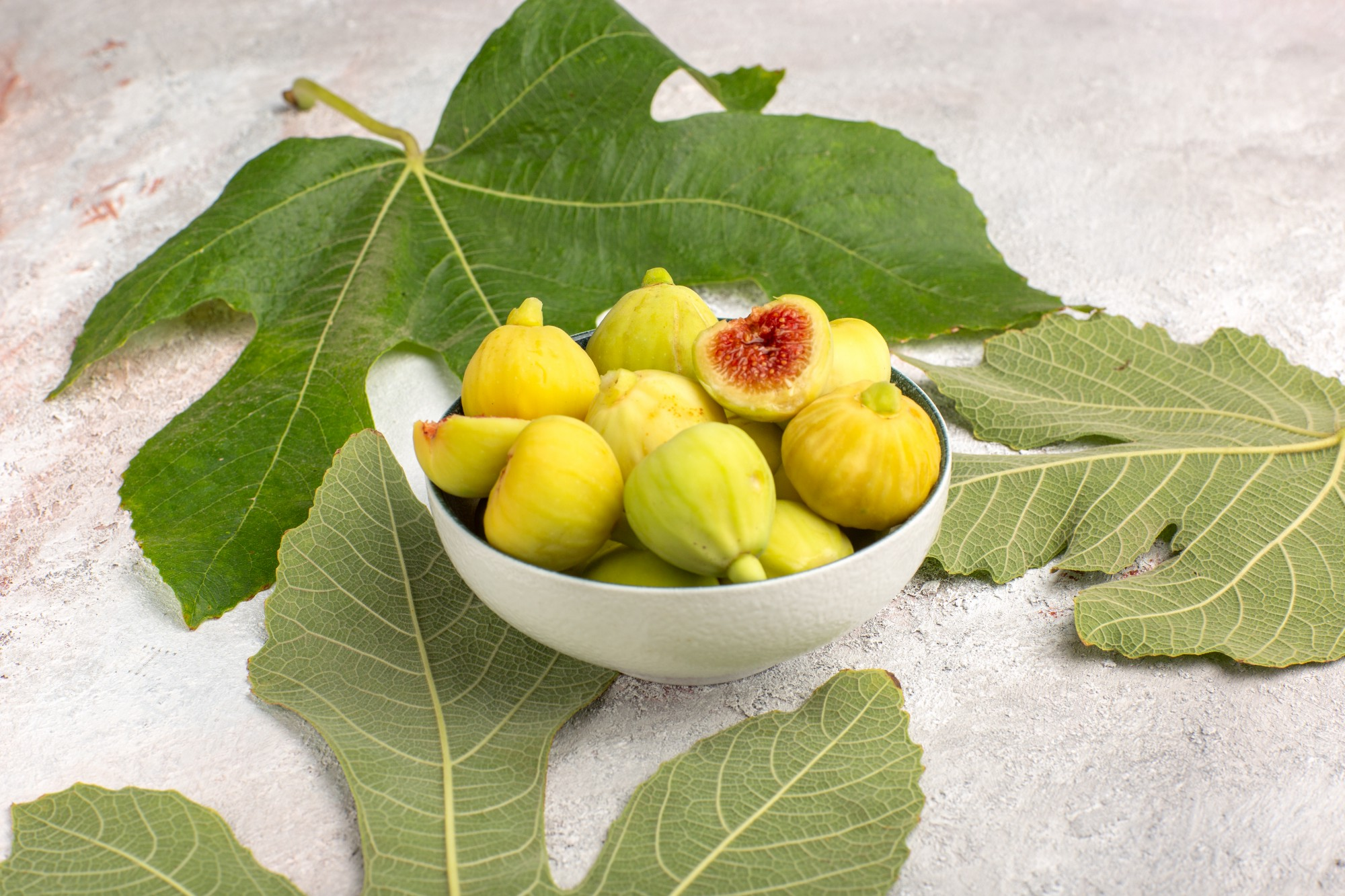 Fig fruit in a bowl surrounded by fig leaves