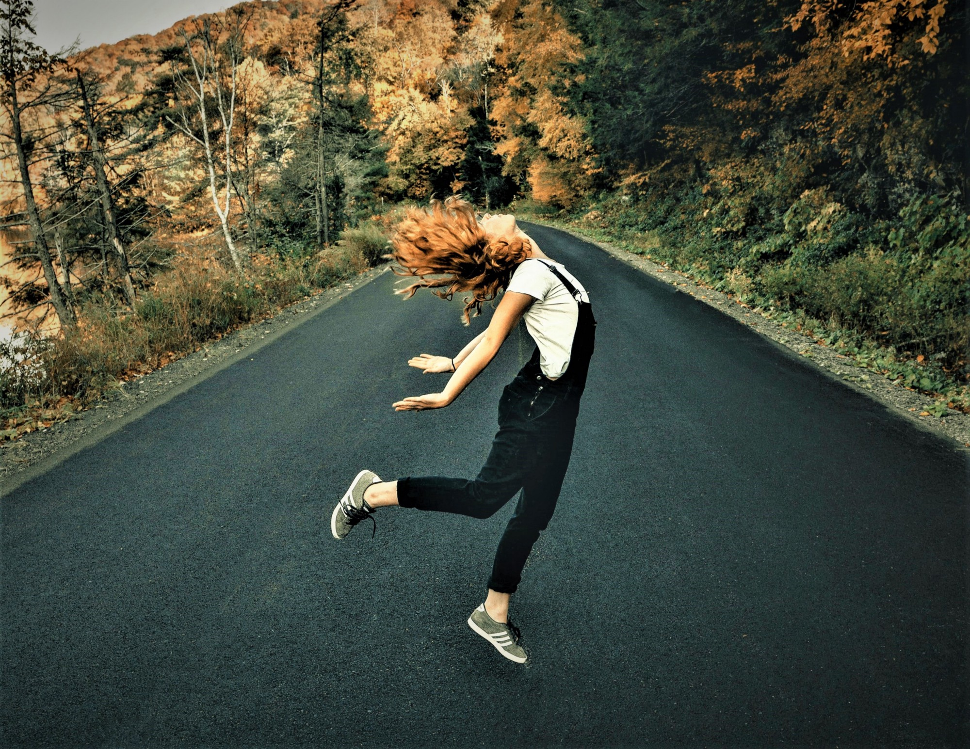 Girl with red hair wearing white shirt and dark overalls jumping in middle of road