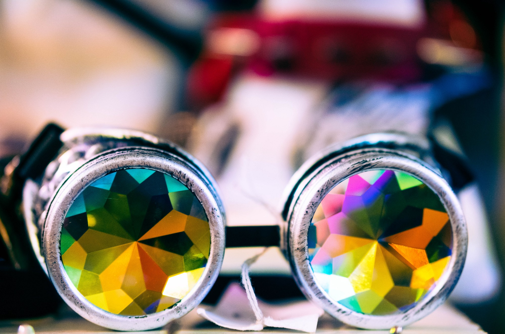 A pair of kaleidoscope glasses with colourful lenses sitting on a table. Background is blurred.