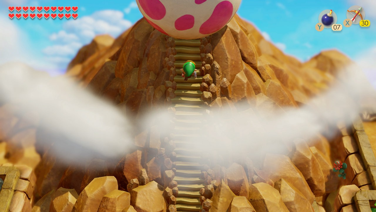 Link approaches the pink-spotted egg of the Wind Fish at the peak of Mt. Tamaranch, above the clouds against a blue sky.