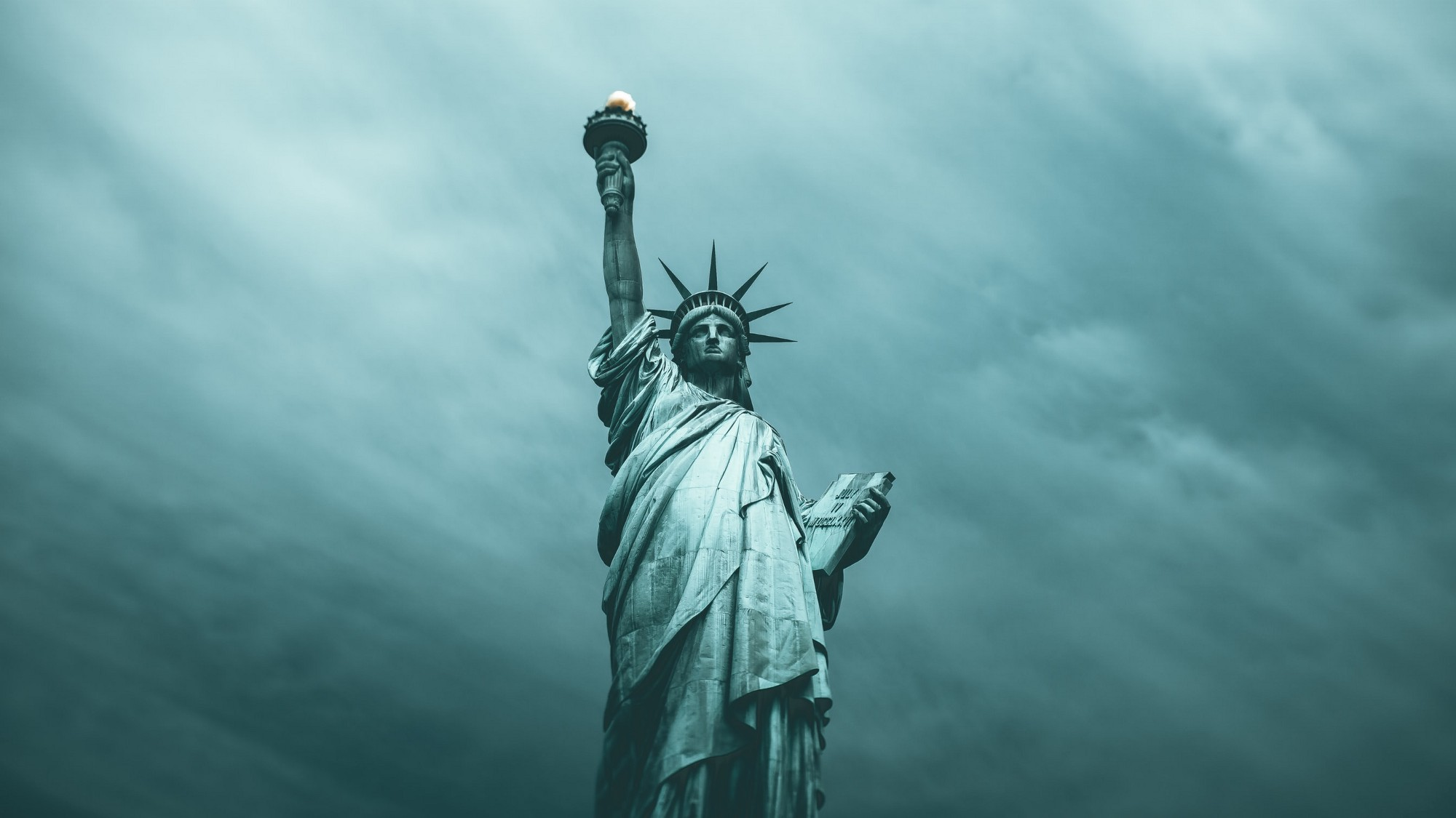 Ethereal green shifted photo of the statue of liberty against a luminous cloudy sky.