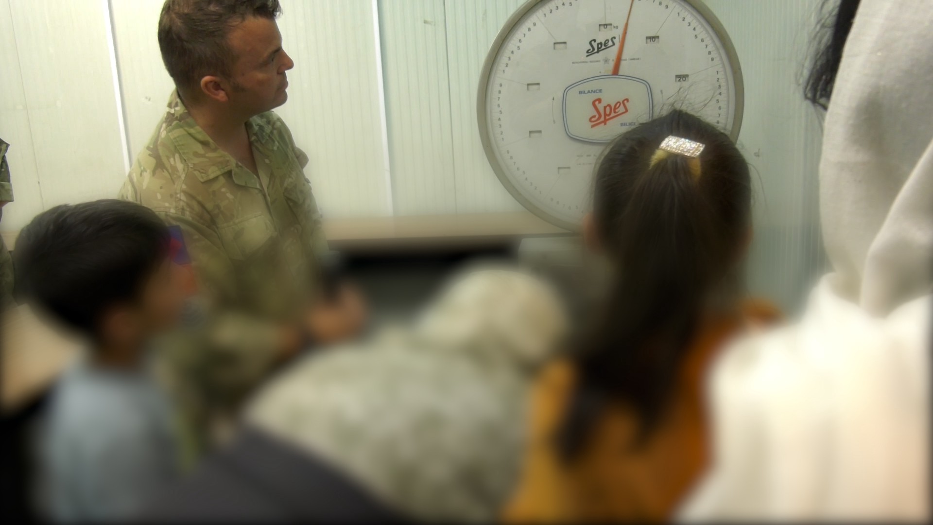 A man in military uniform with a group of people with their backs to the camera looking at a weighing scale.