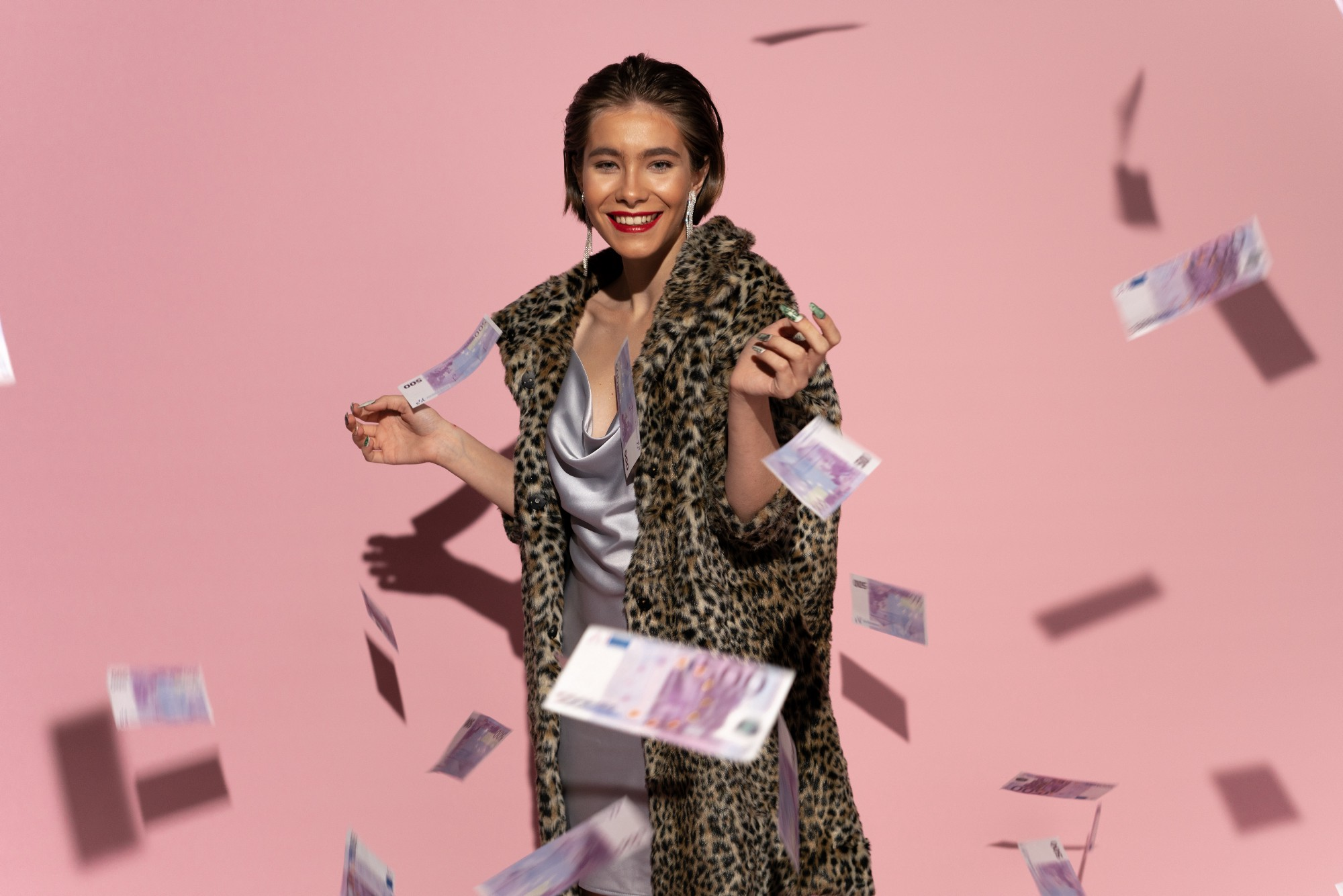 Women wear an expensive brown jacket and she is surrounded by money. She looks happy and looks at the camera.