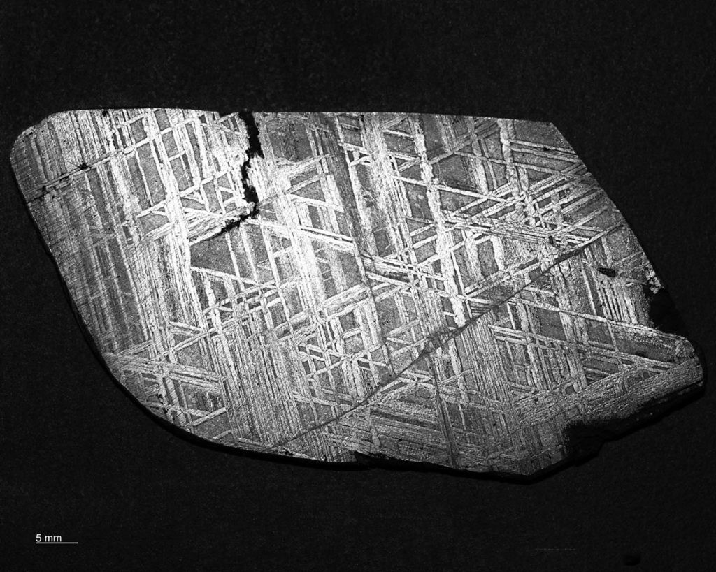 his is a macro photograph of the Muonionalusta meteorite in the ground and etched condition showing the Wedmanstatten structure. The diagonal line in the lower right hand zone of the specimen is a prior-Taenite grain boundary.