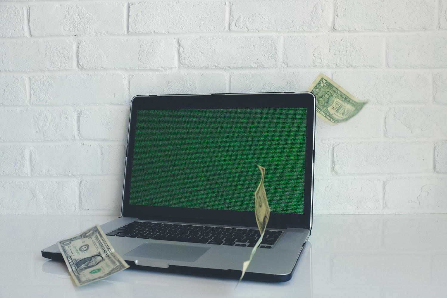 Laptop with dollar bills in the air.