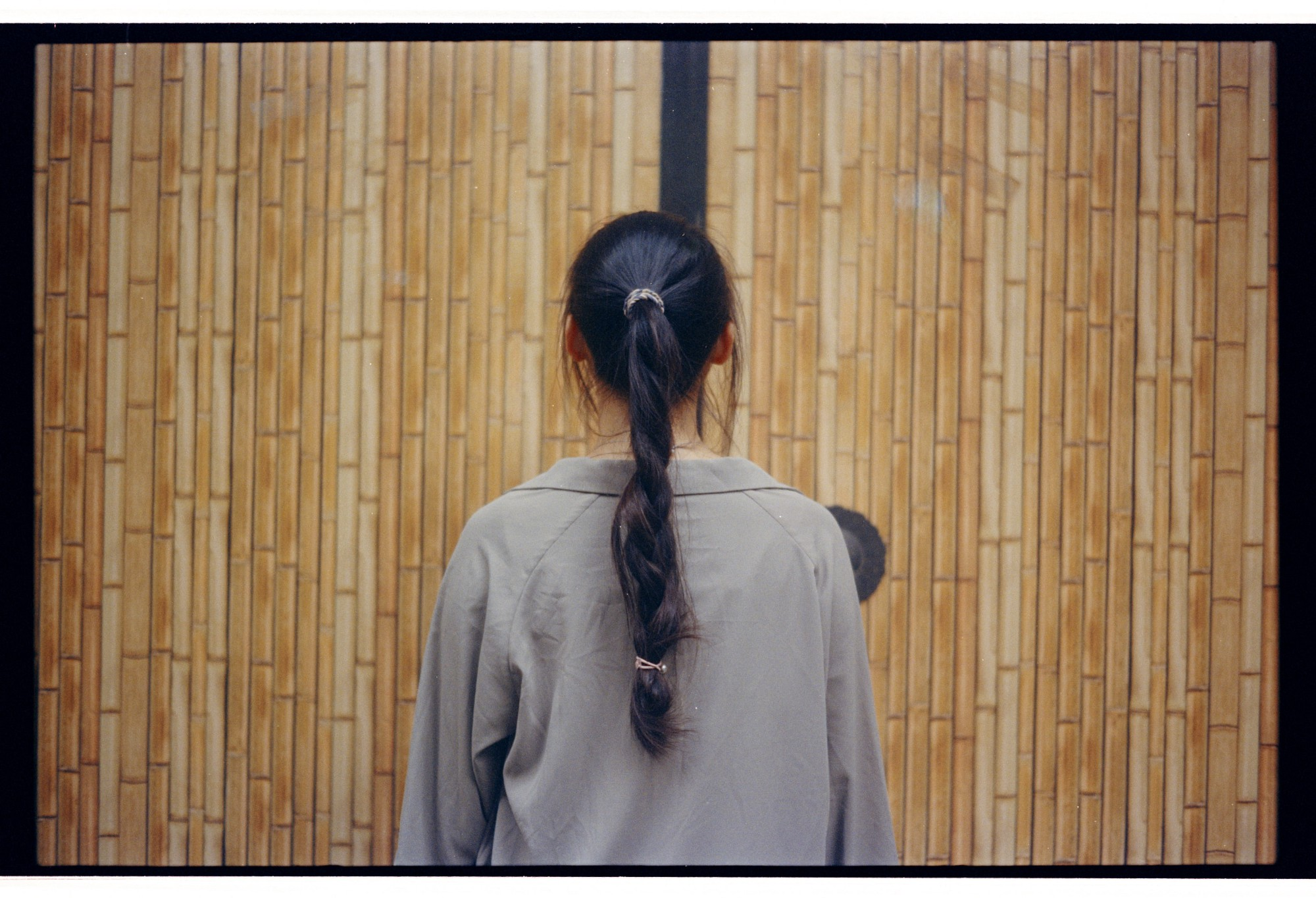 Person with long braid, wearing gray top,  facing closed bamboo door