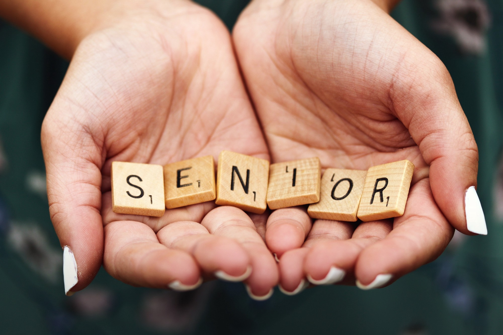 picture of pair of hands holding scrabble pieces spelling Senior