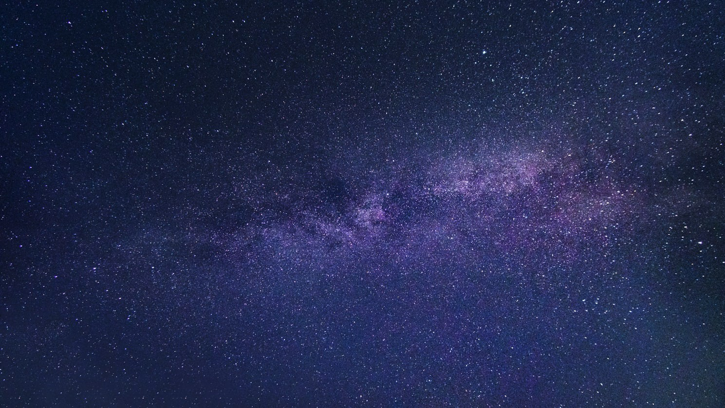 Photo of the Milky Way as seen from Earth in the night sky, in shades of blue and purple