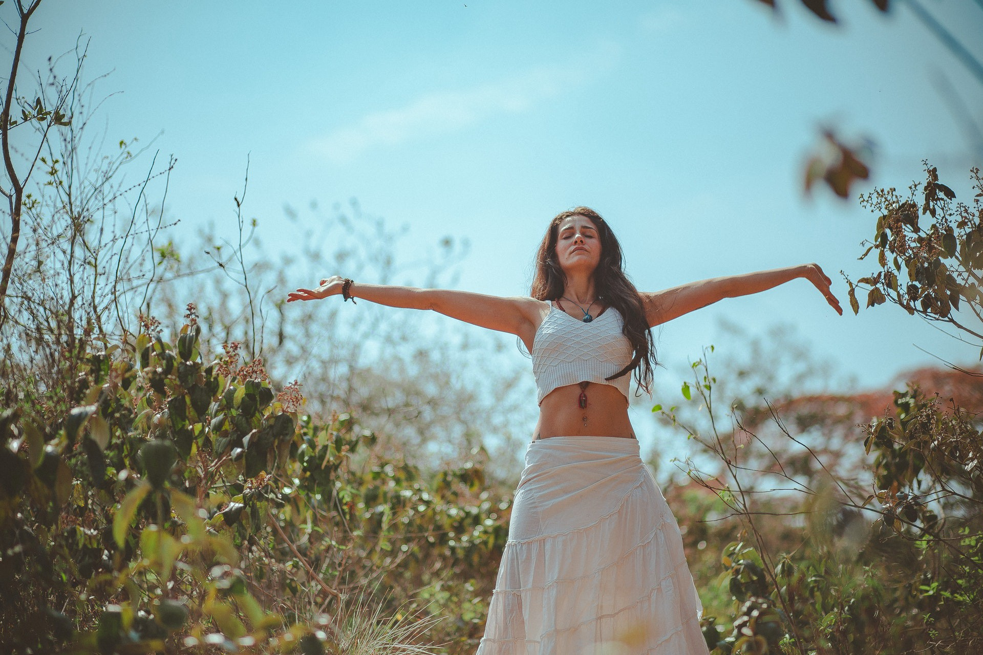 A woman dressed in white linen does a yoga pose in a field.