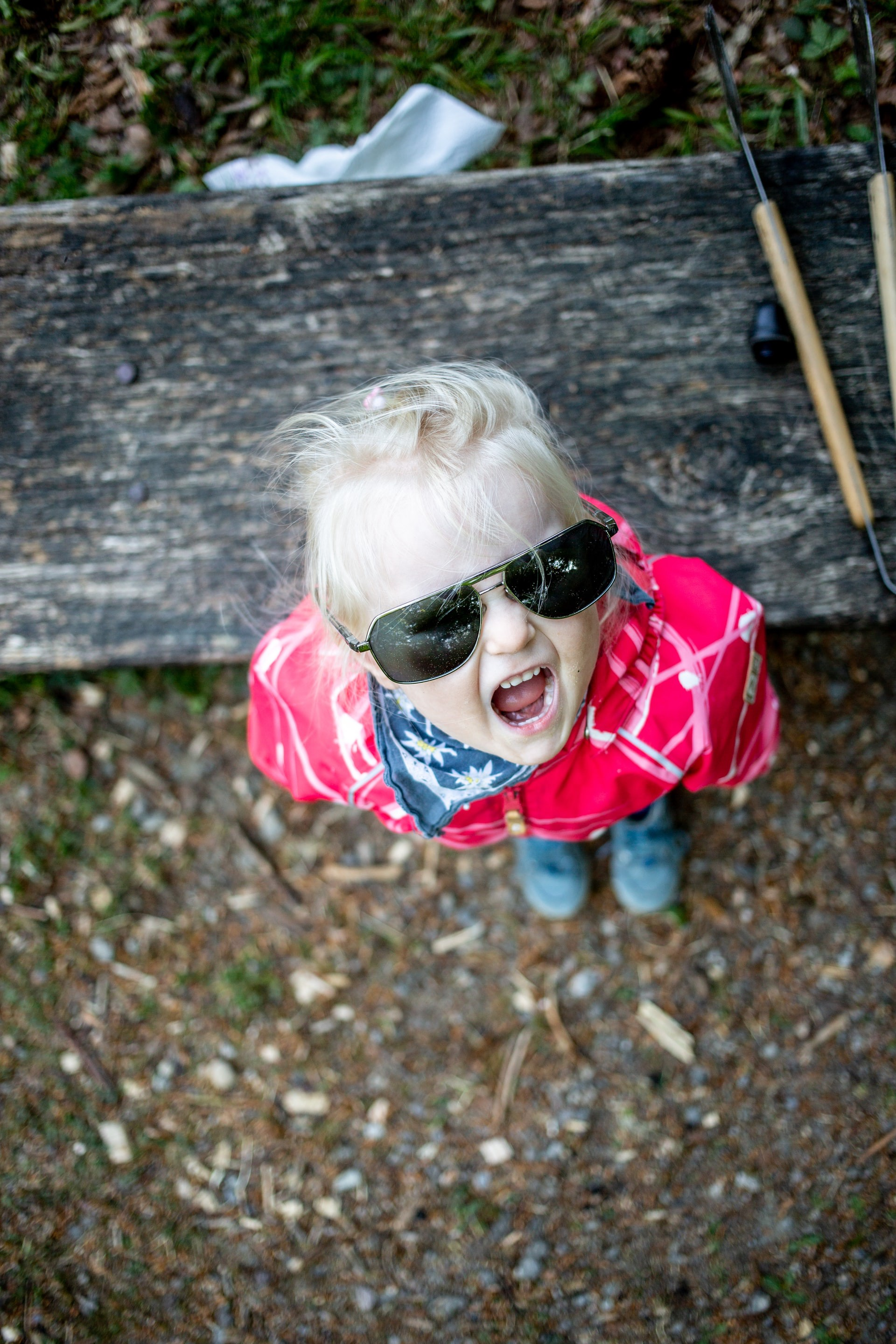 Child wearing sunglasses looking up at the camera with mouth open.