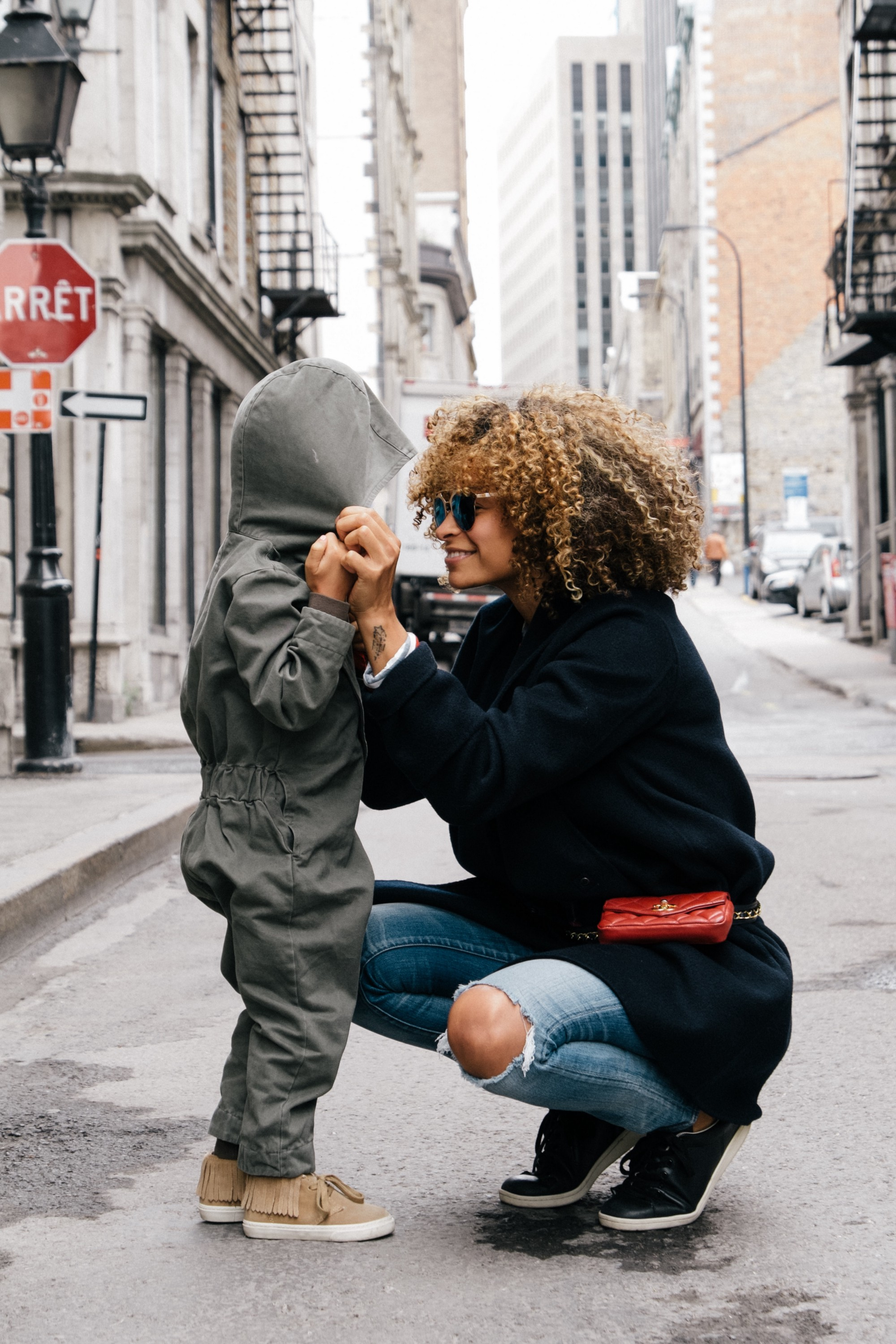 Woman crouching in the street smiling at a child wearing a grey hooded coat. Photo by Sai De Silva on Unsplash