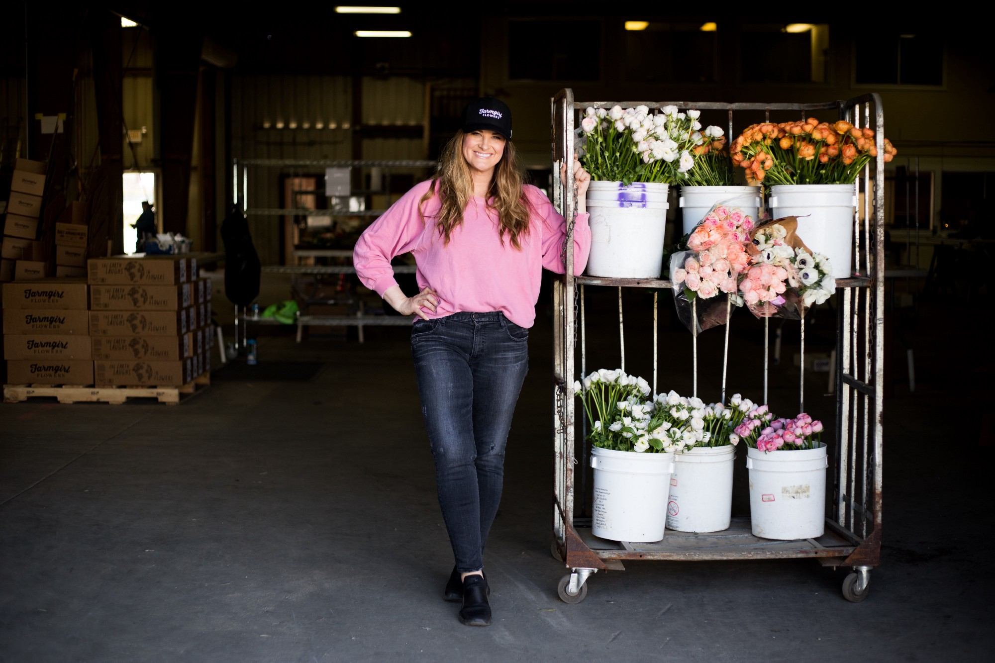 Christina Stembel stands next to various flowers in their warehouse.
