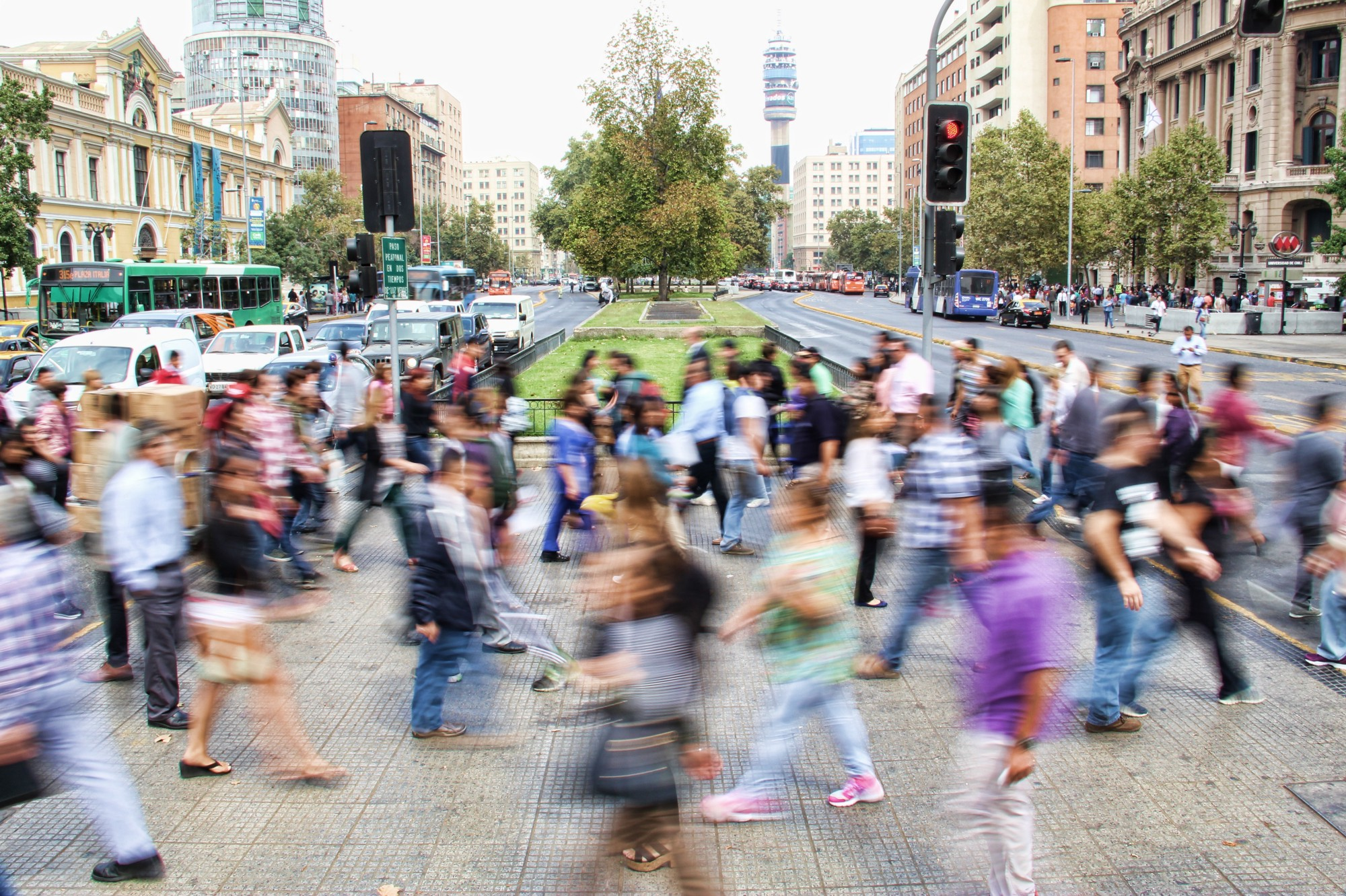 A crowd of people cross paths as they cross an urban street.