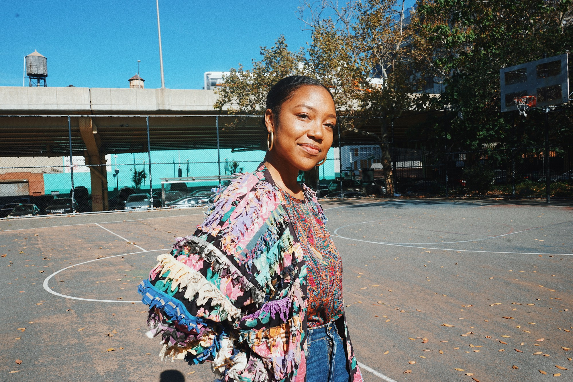A Black woman smiles at the camera. She is standing outside in the sun on a basketball court.