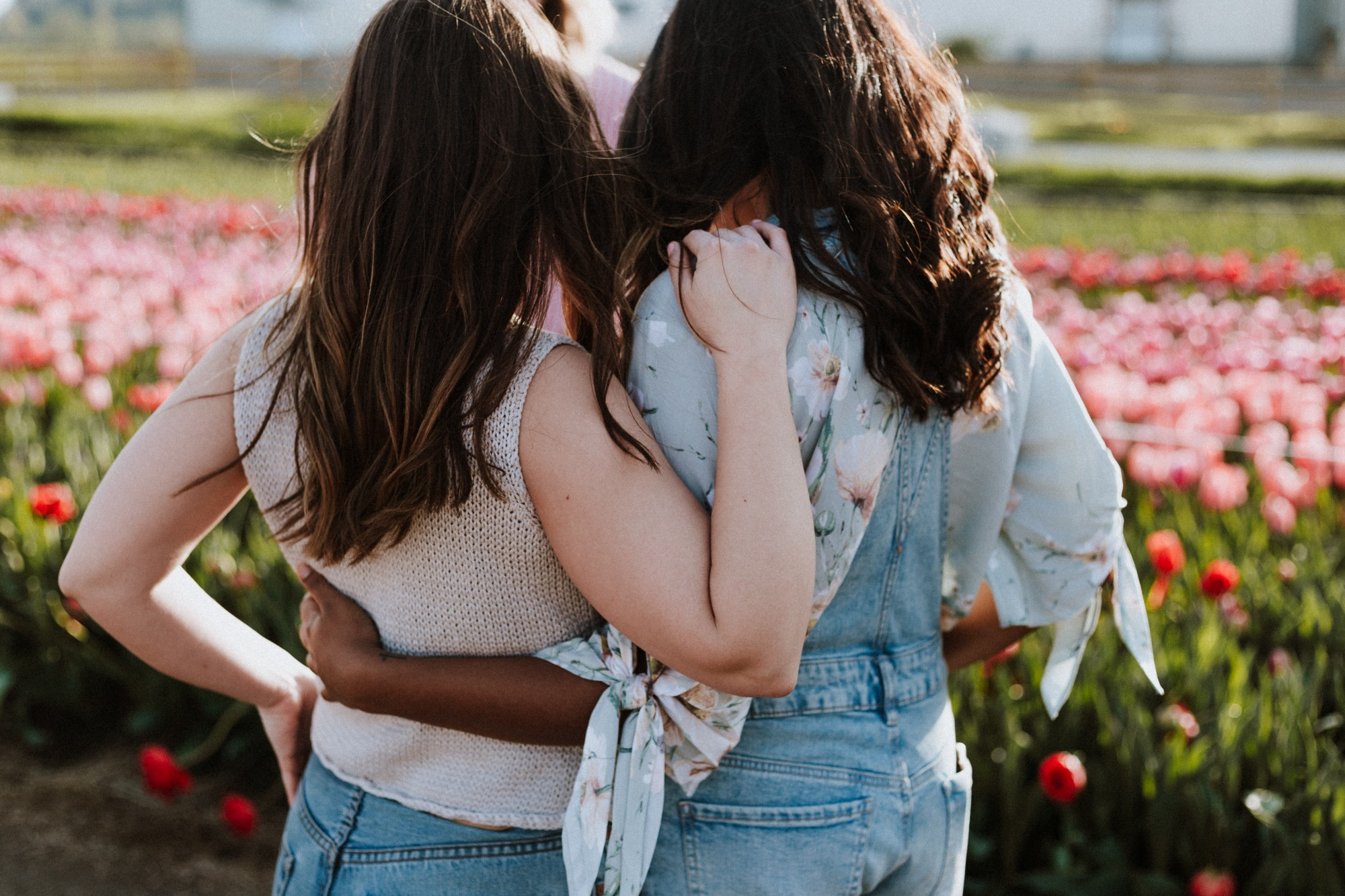 Two female friends with arms wrapped around each other looking out at a field of flowers