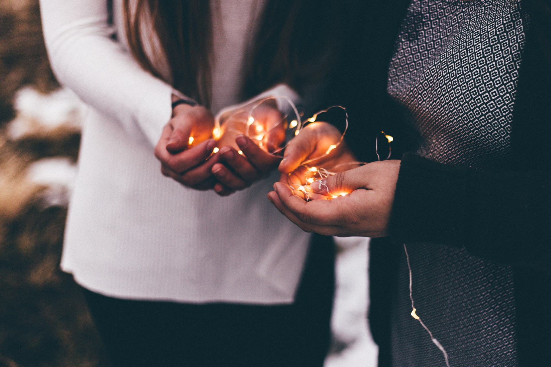 Close-up photo of two person holding lighted string lights.