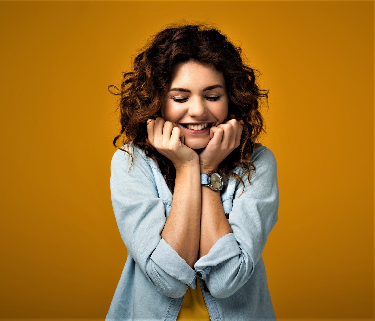 smiling girl with curly brown hair wearing long sleeve light blue shirt holding hands to her face with eyes closed