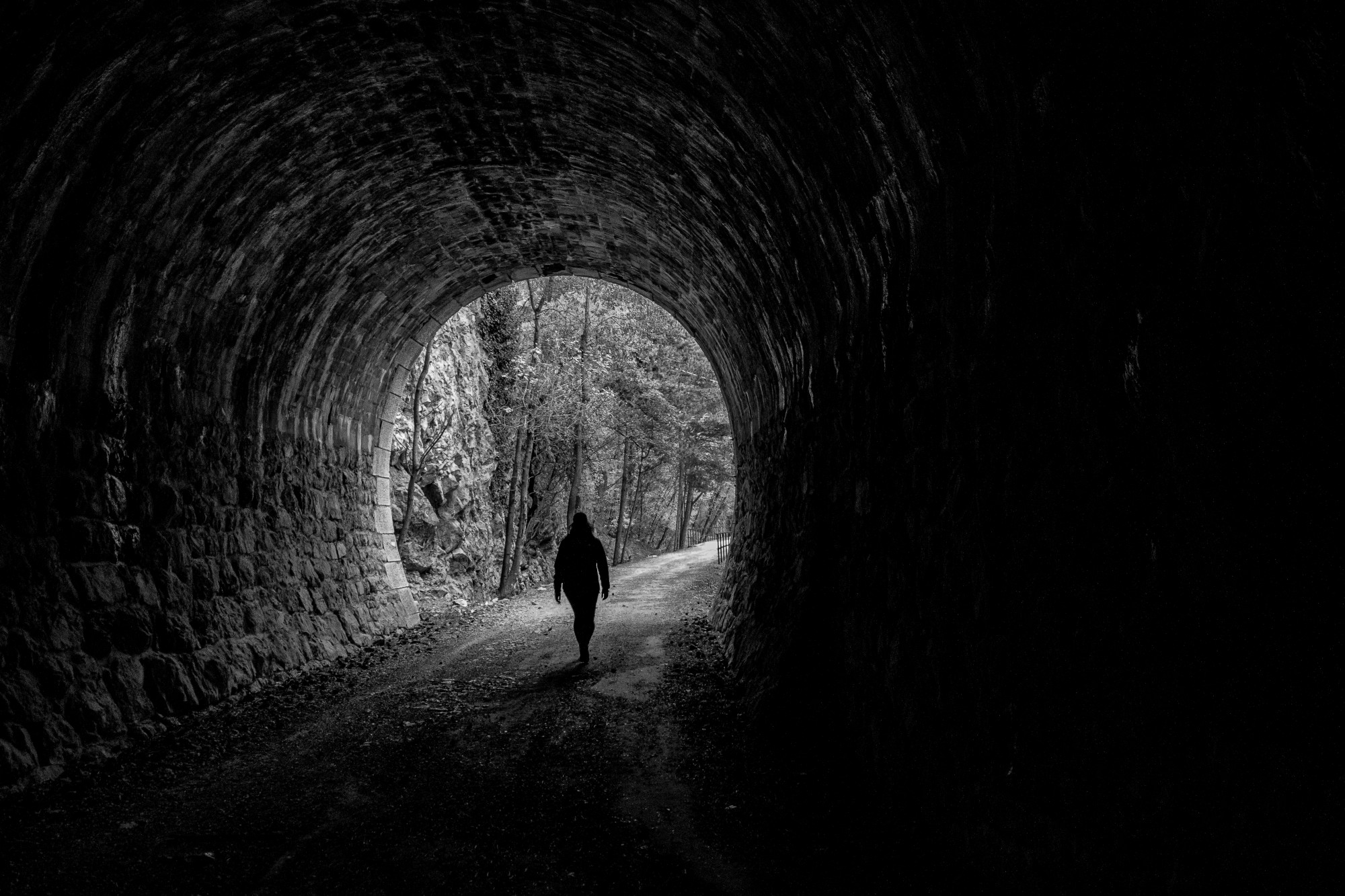 Sillouette of a person leaving a tunnel and walking into a forest.
