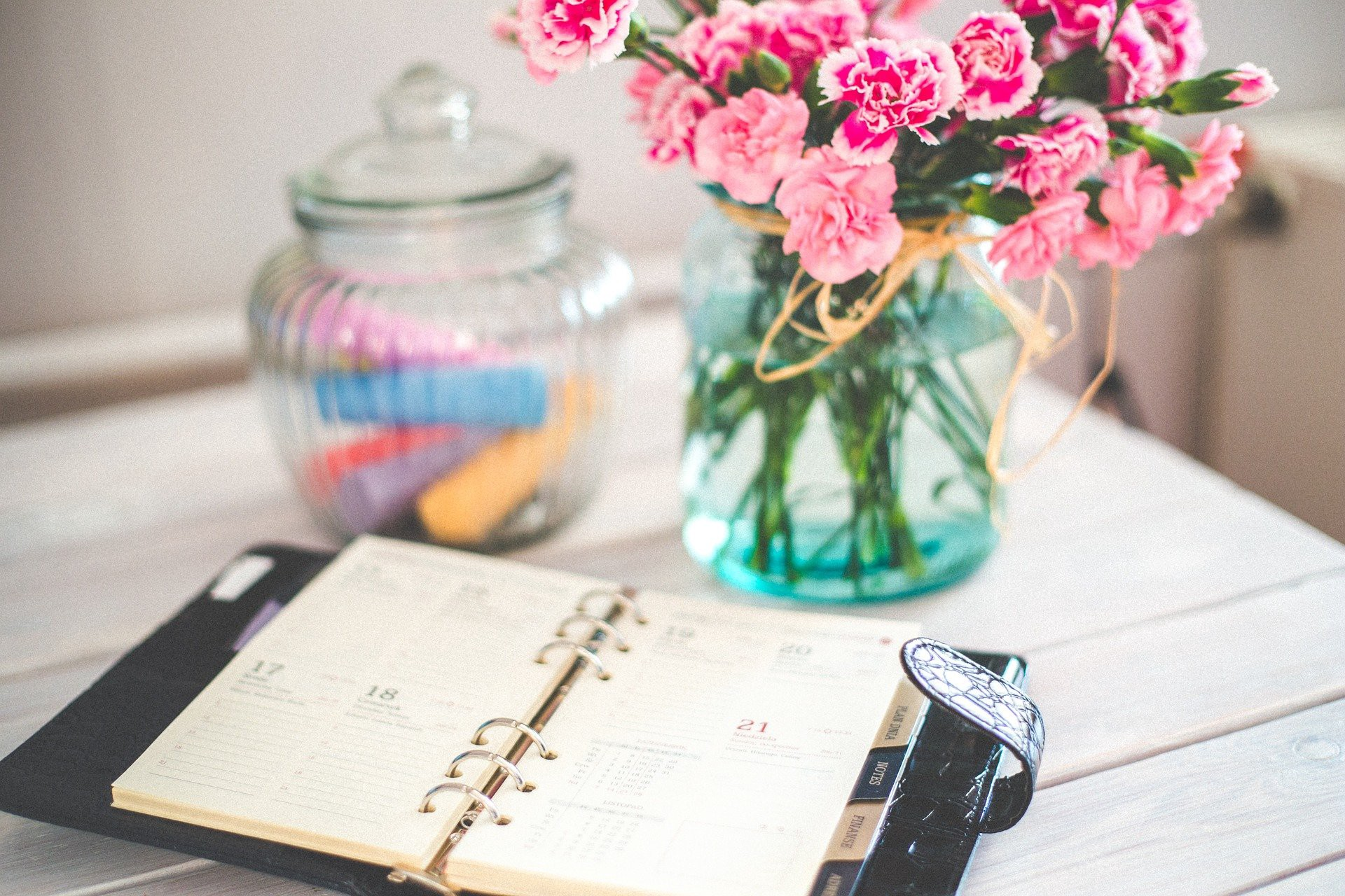 A vase of pink flowers and a notebook on a table