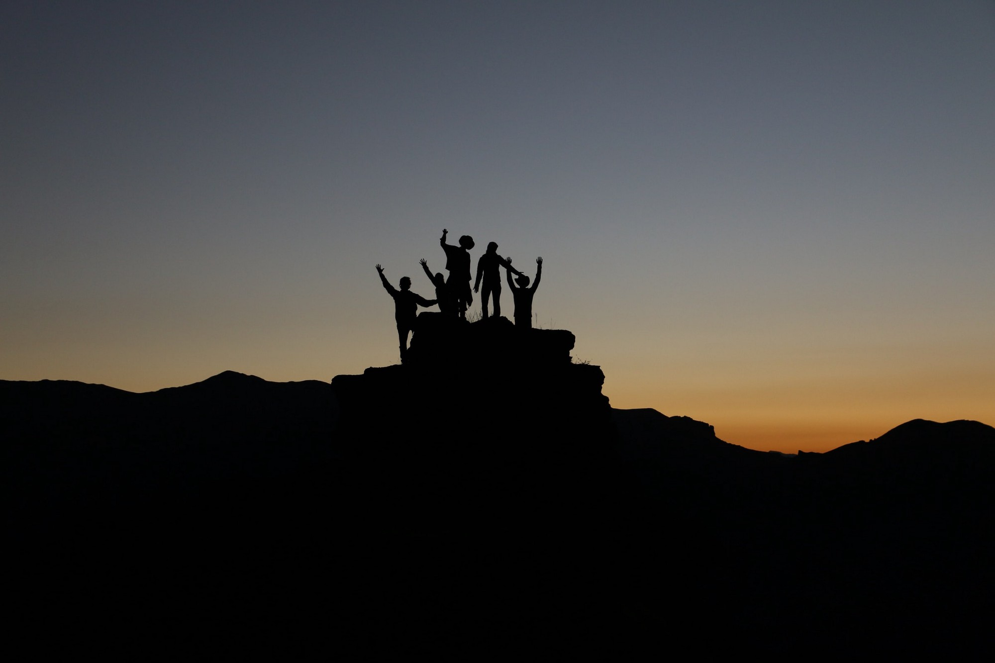 Picture of a group of people, a team, celebrating in the top of a mountain