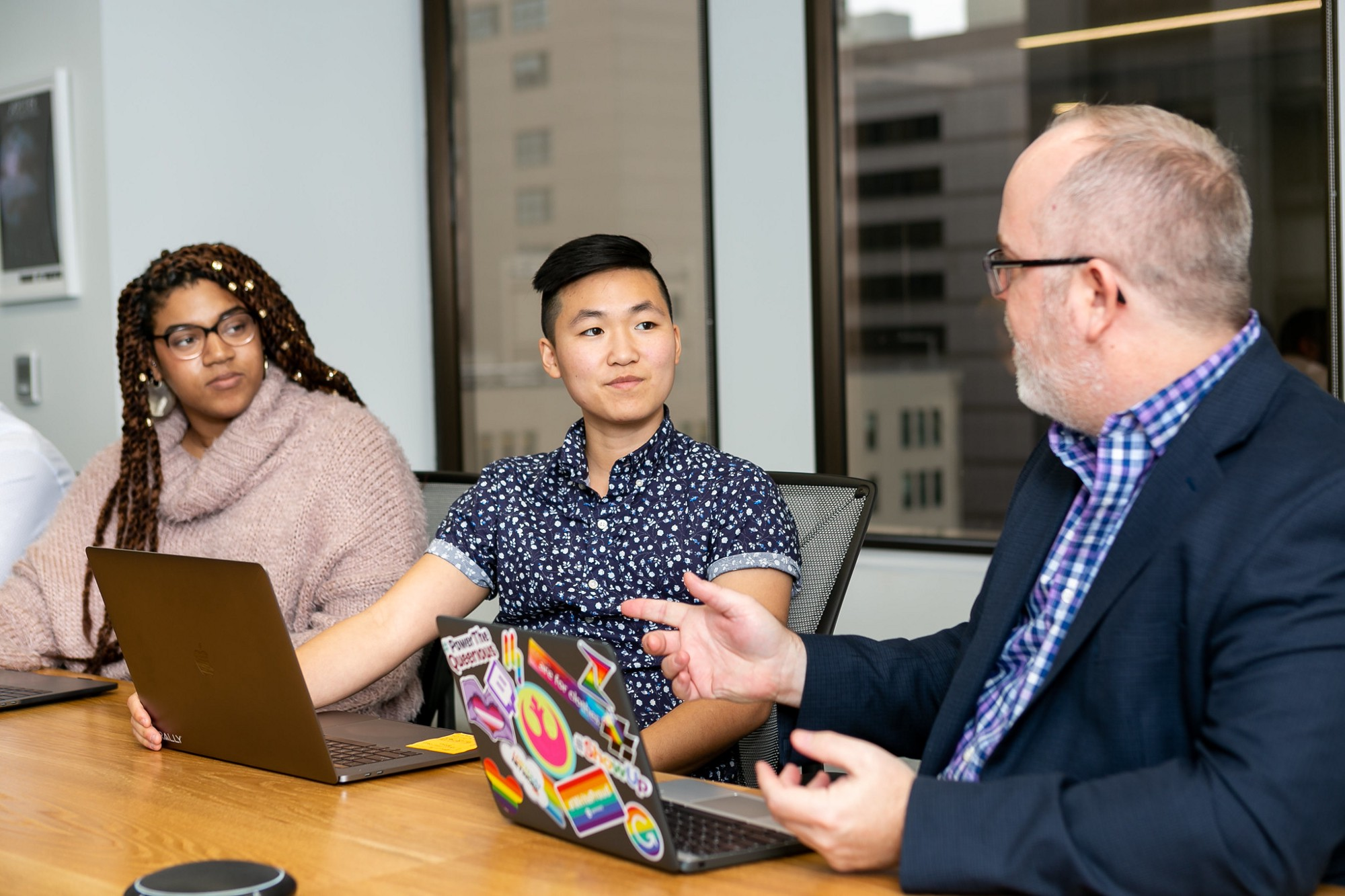 3 people, sitting at a conference table, with their laptops, talking to each other